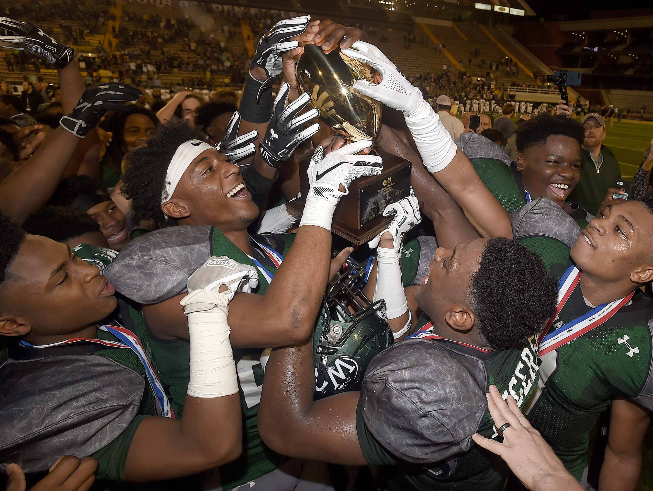 The West Point Green Wave celebrate with the Class 5A trophy after beating West Jones on Saturday, December 1, 2018, in the MHSAA BlueCross BlueShield Gridiron Classic High School Football Championships in M.M. Roberts Stadium on the University of Southern Mississippi campus in Hattiesburg, Miss.