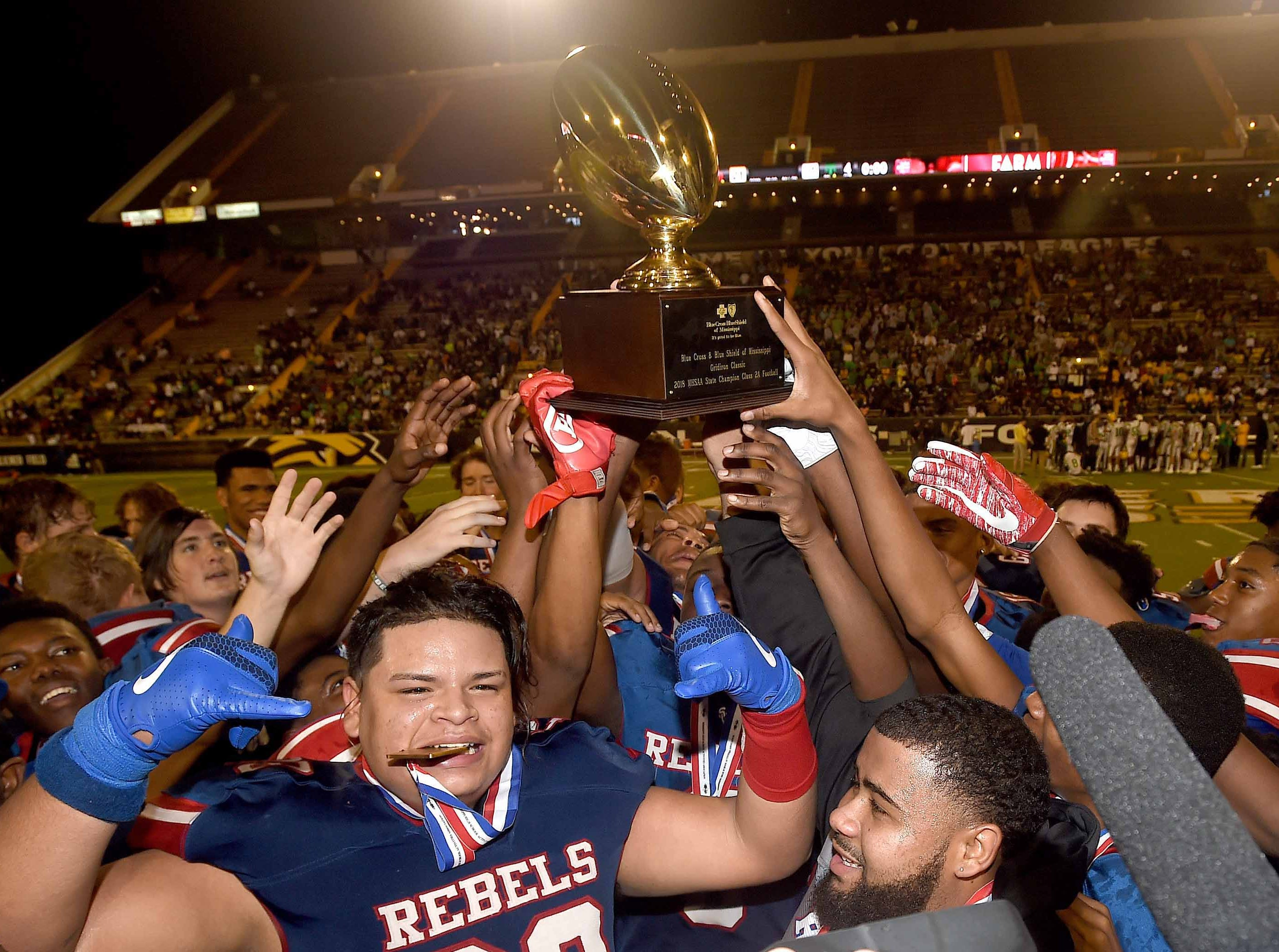 The Scott Central Rebels celebrate with the Class 2A trophy after beating Taylorsville on Saturday, December 1, 2018, in the MHSAA BlueCross BlueShield Gridiron Classic High School Football Championships in M.M. Roberts Stadium on the University of Southern Mississippi campus in Hattiesburg, Miss.