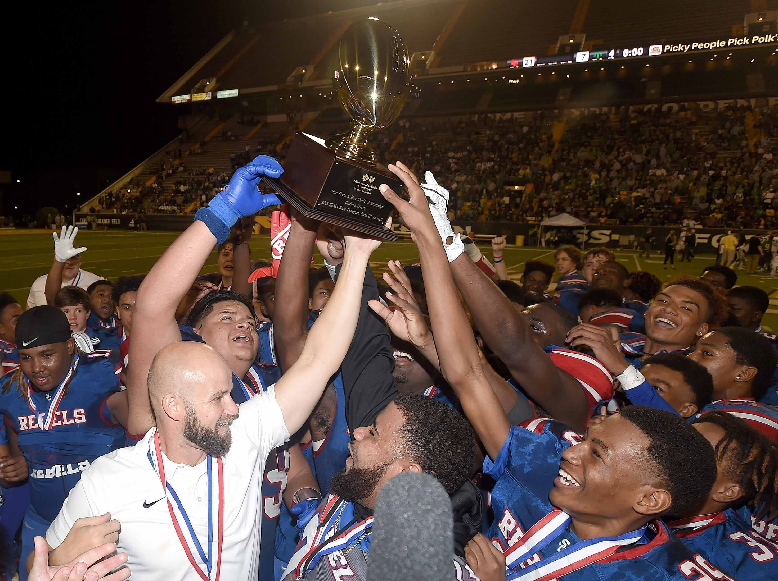 The Scott Central Rebels and head coach Devin Cooper celebrate with the Class 2A trophy after beating Taylorsville on Saturday, December 1, 2018, in the MHSAA BlueCross BlueShield Gridiron Classic High School Football Championships in M.M. Roberts Stadium on the University of Southern Mississippi campus in Hattiesburg, Miss.
