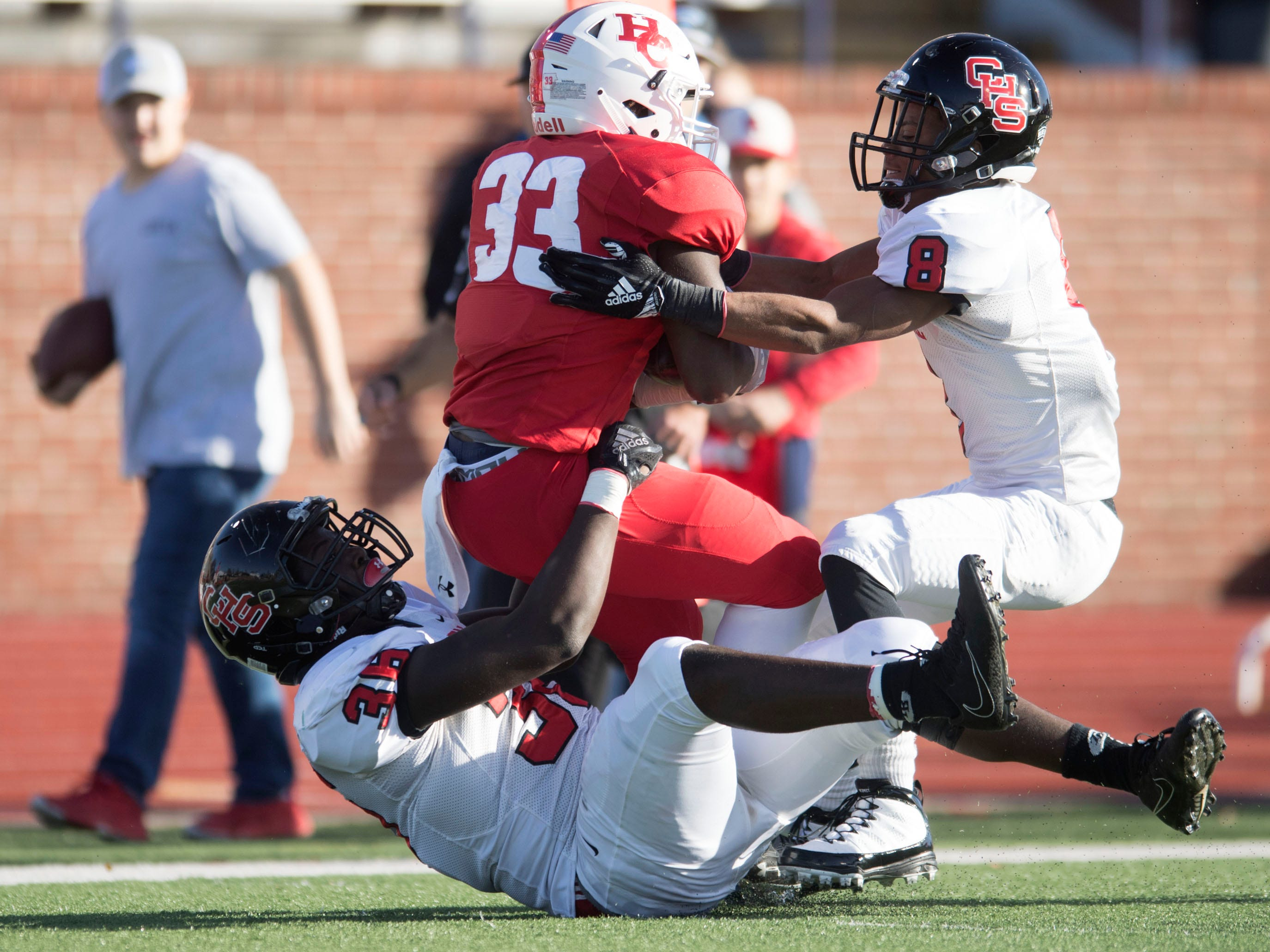 Henry County's Donovan Teague (33) is tackled by Knoxville Central's Deonte Middleton (36) and Daunte Holliday (8) in the Class 5A BlueCross Bowl at Tucker Stadium on Sunday, December 2, 2018.