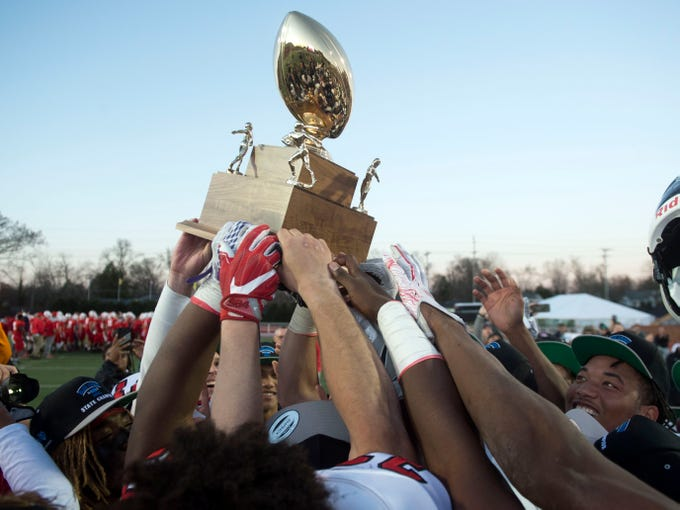 Knoxville Central hoists their championship trophy after beating Henry County in the Class 5A BlueCross Bowl at Tucker Stadium on Sunday, December 2, 2018.