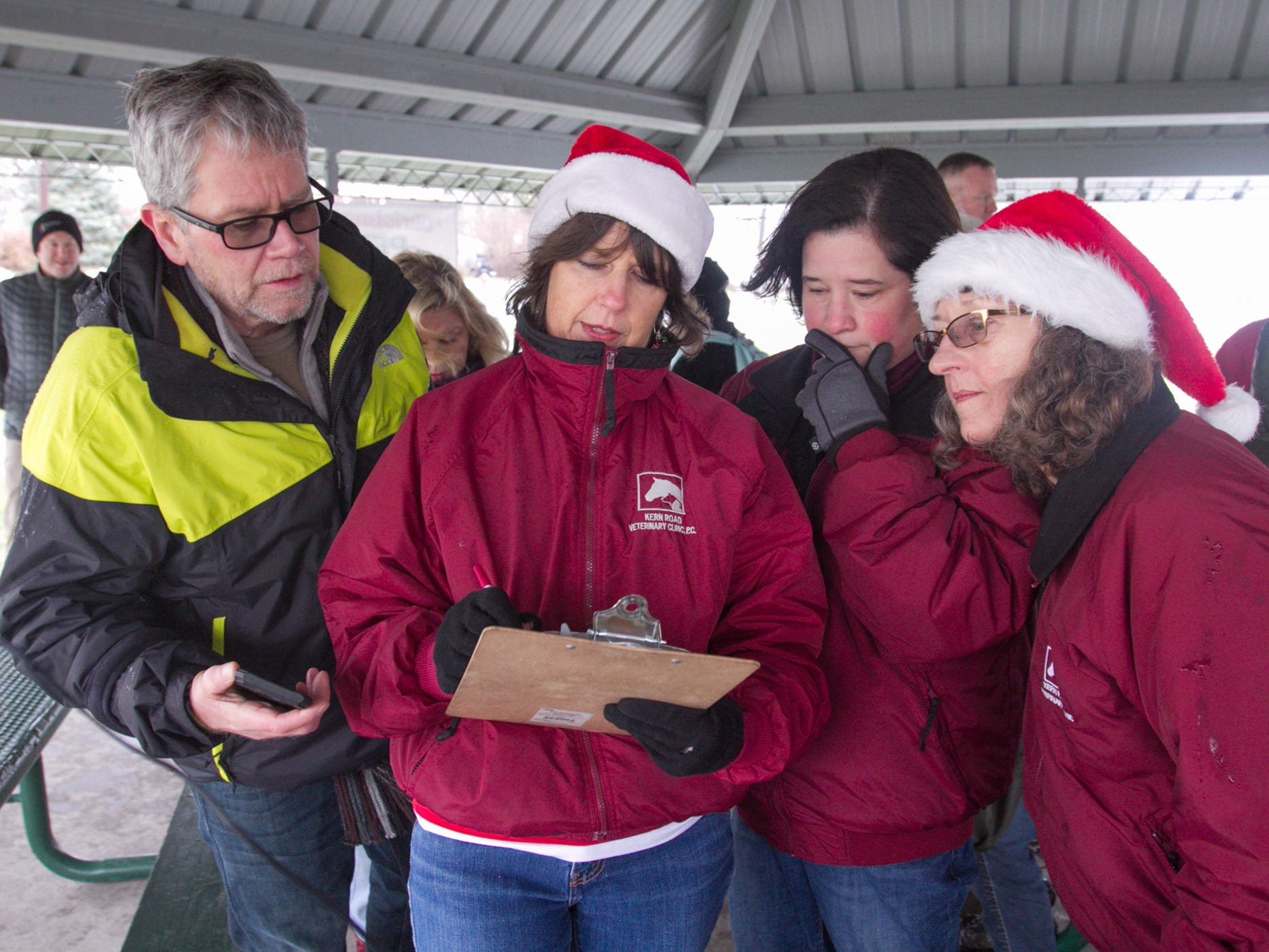 From left, Brian Nordyke, Amy Kirchen, Dr. Bernadette Hermann and Jennifer Koprince of the Kern Road Veterinary Clinic confer on the judging of the pet parade at the Christmas in the 'Ville Saturday, Dec. 1, 2018.
