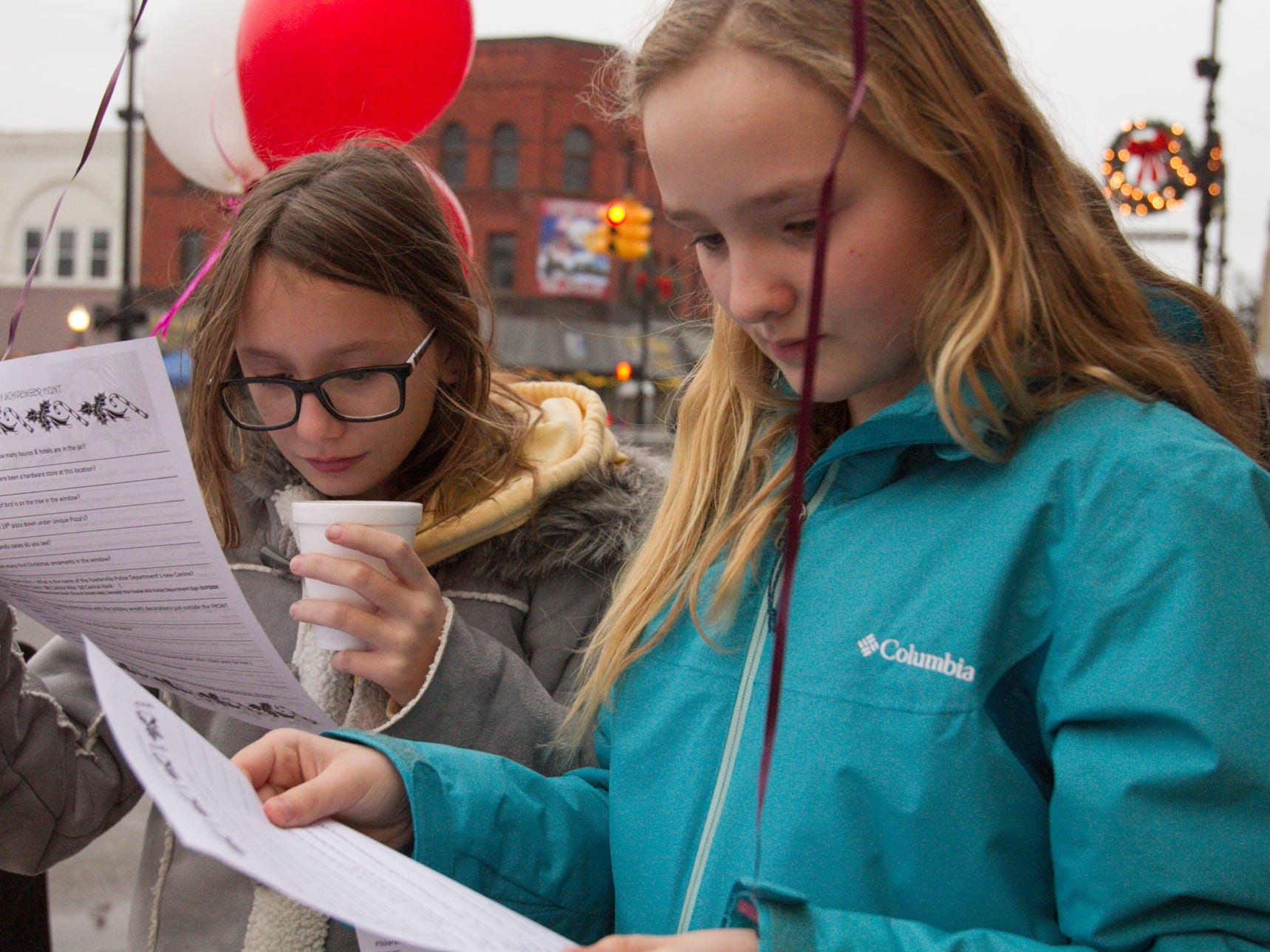 11-year-old friends Chloe Smith and Adreana Smith check out the challenge of the scavenger hunt, part of the Christmas in the 'Ville festivities Saturday, Dec. 1, 2018.