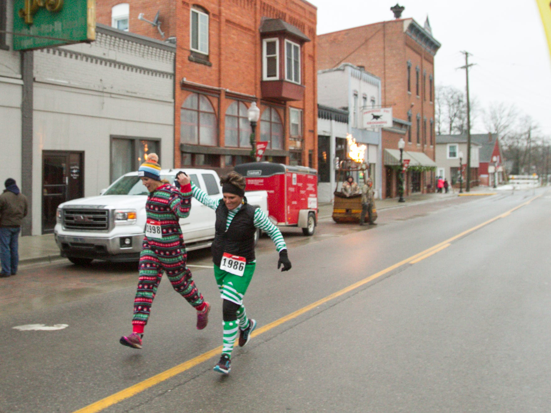 Jen Merritt of Rochester Hills, left, and Kelly Moran of Onaway, strangers at the start of the Dashing Through the Snow 5k, support one another through the finish line Saturday, Dec. 1, 2018 at Christmas in the 'Ville.