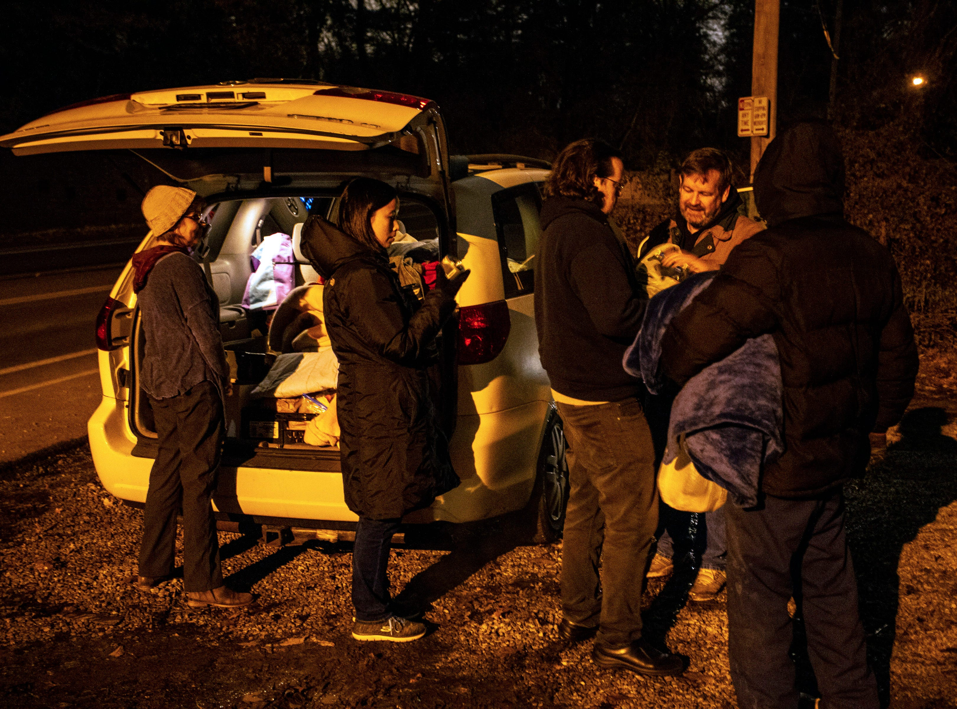 Volunteers make a stop along a darkened stretch of Lexington Avenue to distribute items to the homeless living in nearby wooded areas. 11/26/18