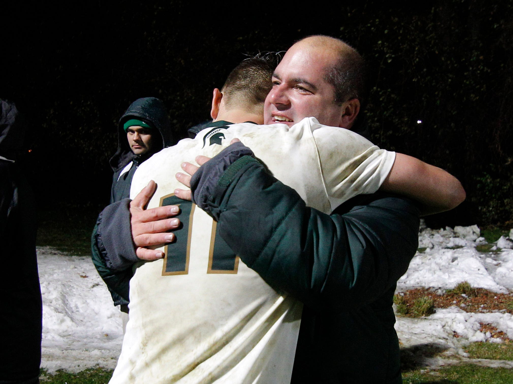 Michigan State's Ryan Sierakowski, left, and coach Damon Rensing hug following a 2-1 win over James Madison, Saturday, Dec. 1, 2018, in East Lansing, Mich. Sierakowski scored both of MSU's goals.
