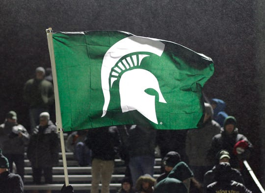Fans hold a Michigan State flag as the Spartans take on James Madison in their Elite 8 NCAA game, Saturday, Dec. 1, 2018, in East Lansing, Mich. Michigan State won 2-1.