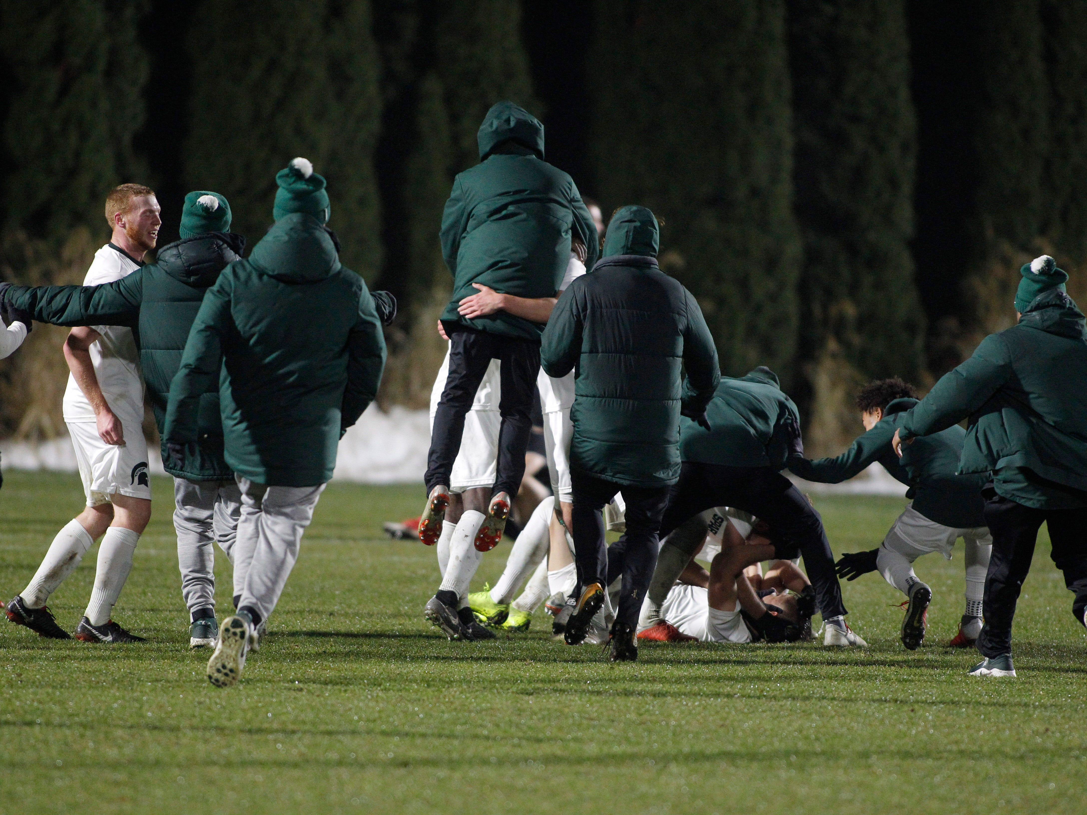 Michigan State players celebrate around Ryan Sierakowski, bottom, after defeating James Madison 2-1, Saturday, Dec. 1, 2018, in East Lansing, Mich.