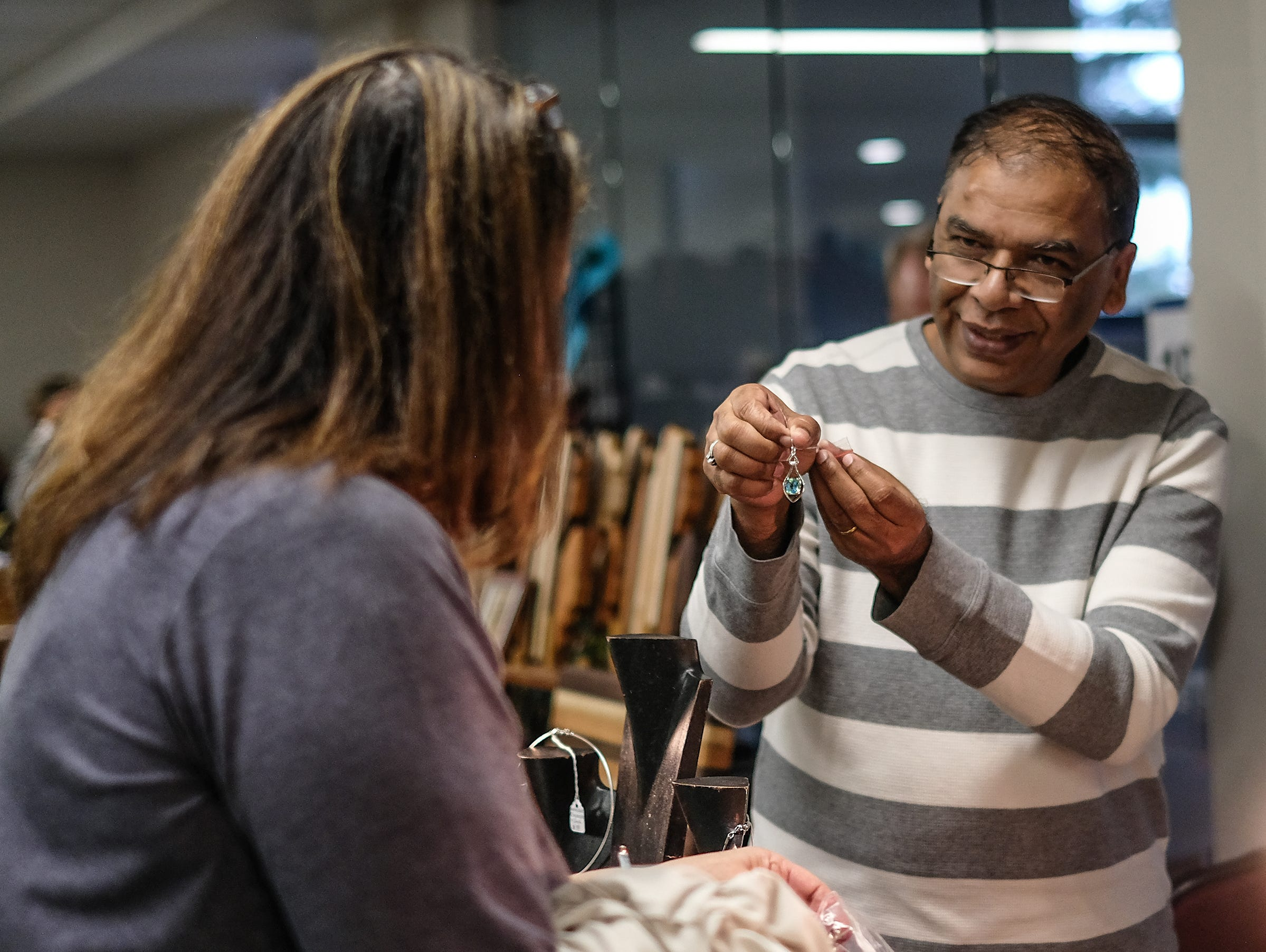 Steven Shaikh of San Martin Design, shows Marilyn Fine from East Lansing some earrings at the MSU Winter Arts & Craft Show Sunday, Dec. 2, 2018. Fine, a regular customer says she has been buying from Shaikn for 16 years at the popular annual event.