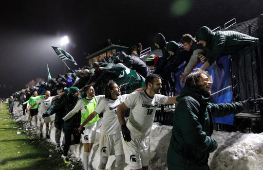 Michigan State players celebrate with fans following their 2-1 win over James Madison, Saturday, Dec. 1, 2018, in East Lansing, Mich. Michigan State won 2-1.