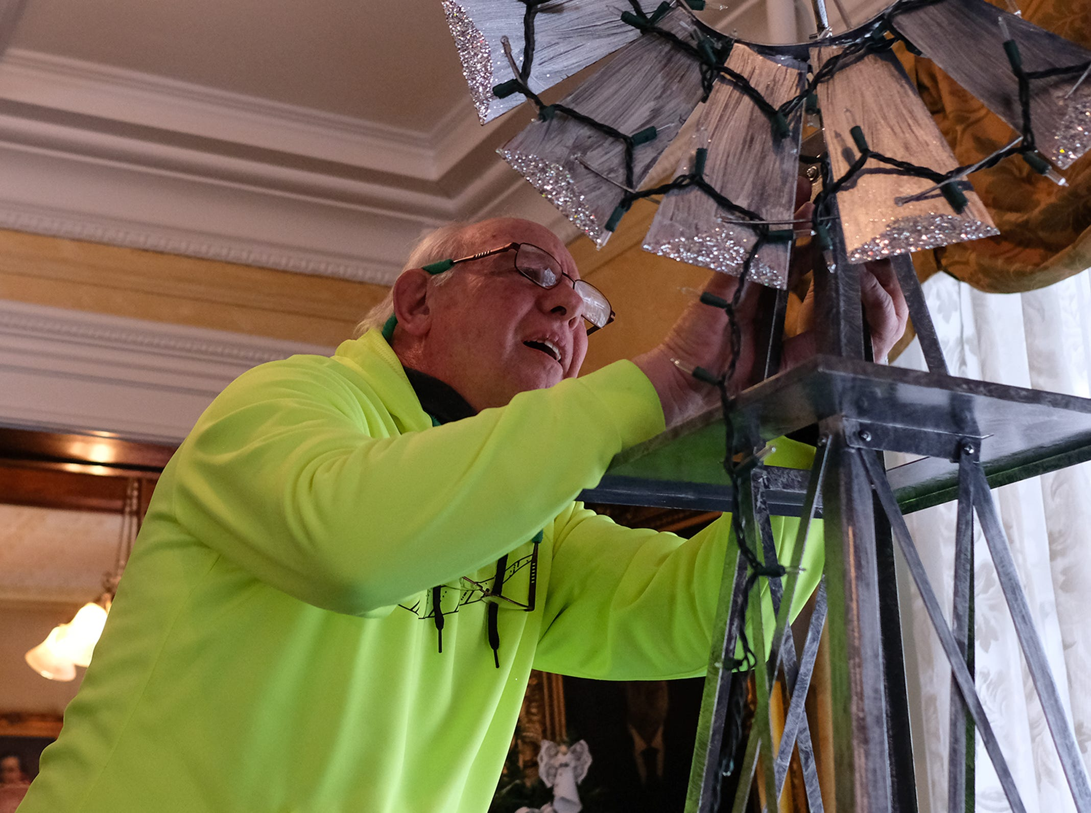 "Craig Gunn works on putiing lights on a windmill as part of the Friends of MSU Theatre's ""Oklahoma"" themed Christmas tree at the Turner-Dodge House in preparation for the annual A Festival of Trees Saturday, Dec. 1, 2018. The event opens December 8th."