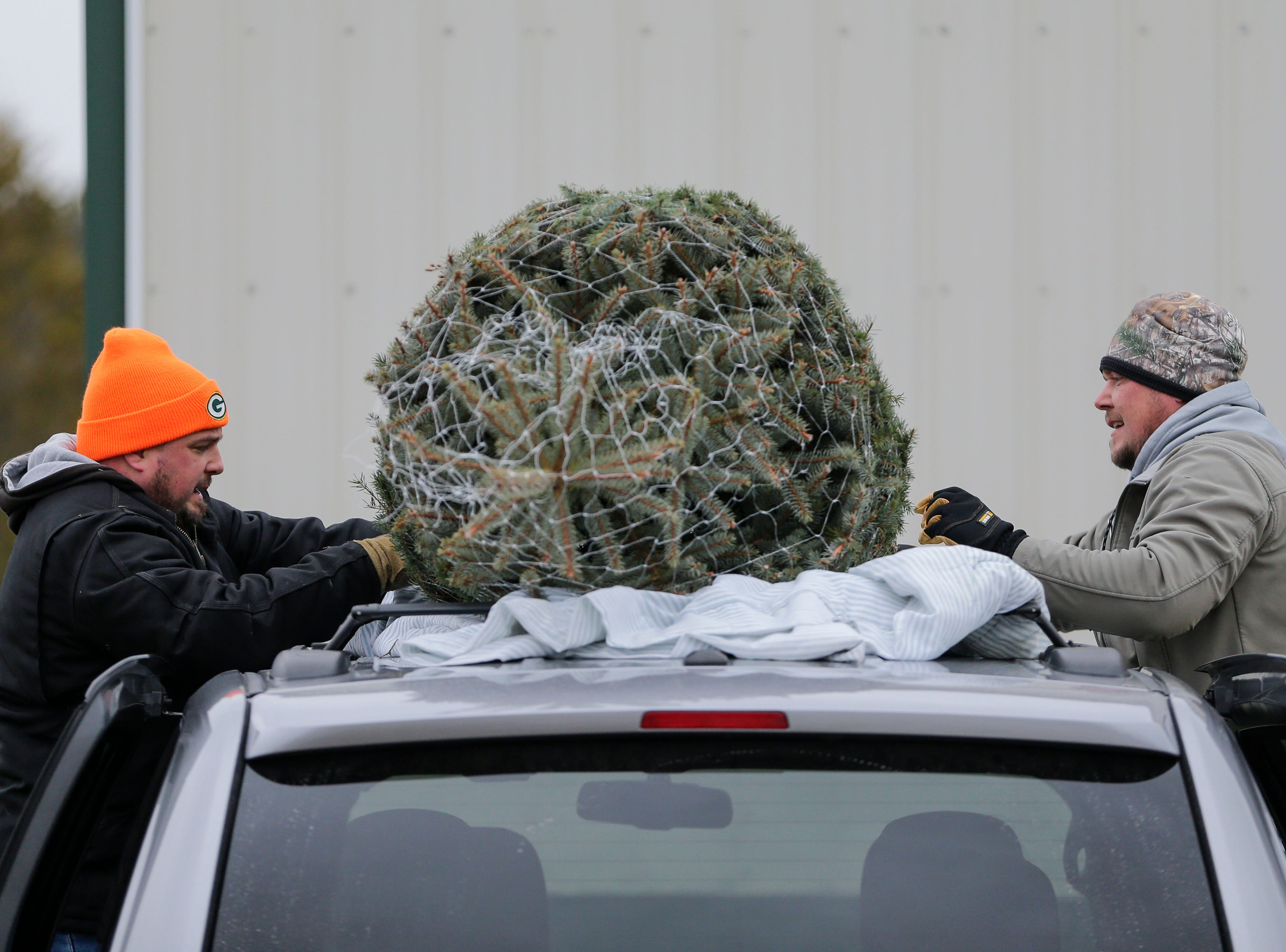 Andy Zigmunt, right, straps his tree to the top of his family's car at Taylor Trees Saturday, December 1, 2018, in Mishicot, Wis. Joshua Clark/USA TODAY NETWORK-Wisconsin