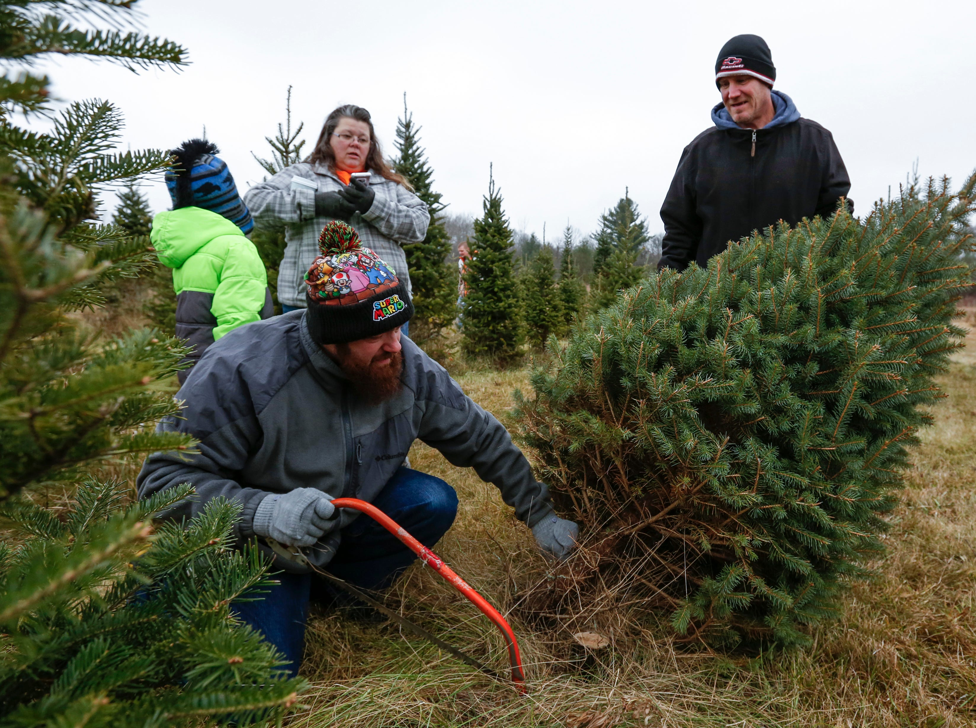 Cody Graham, of Manitowoc, cuts down a Christmas tree with his family as David Schultz keeps it steady at Taylor Trees Saturday, December 1, 2018, in Mishicot, Wis. Joshua Clark/USA TODAY NETWORK-Wisconsin