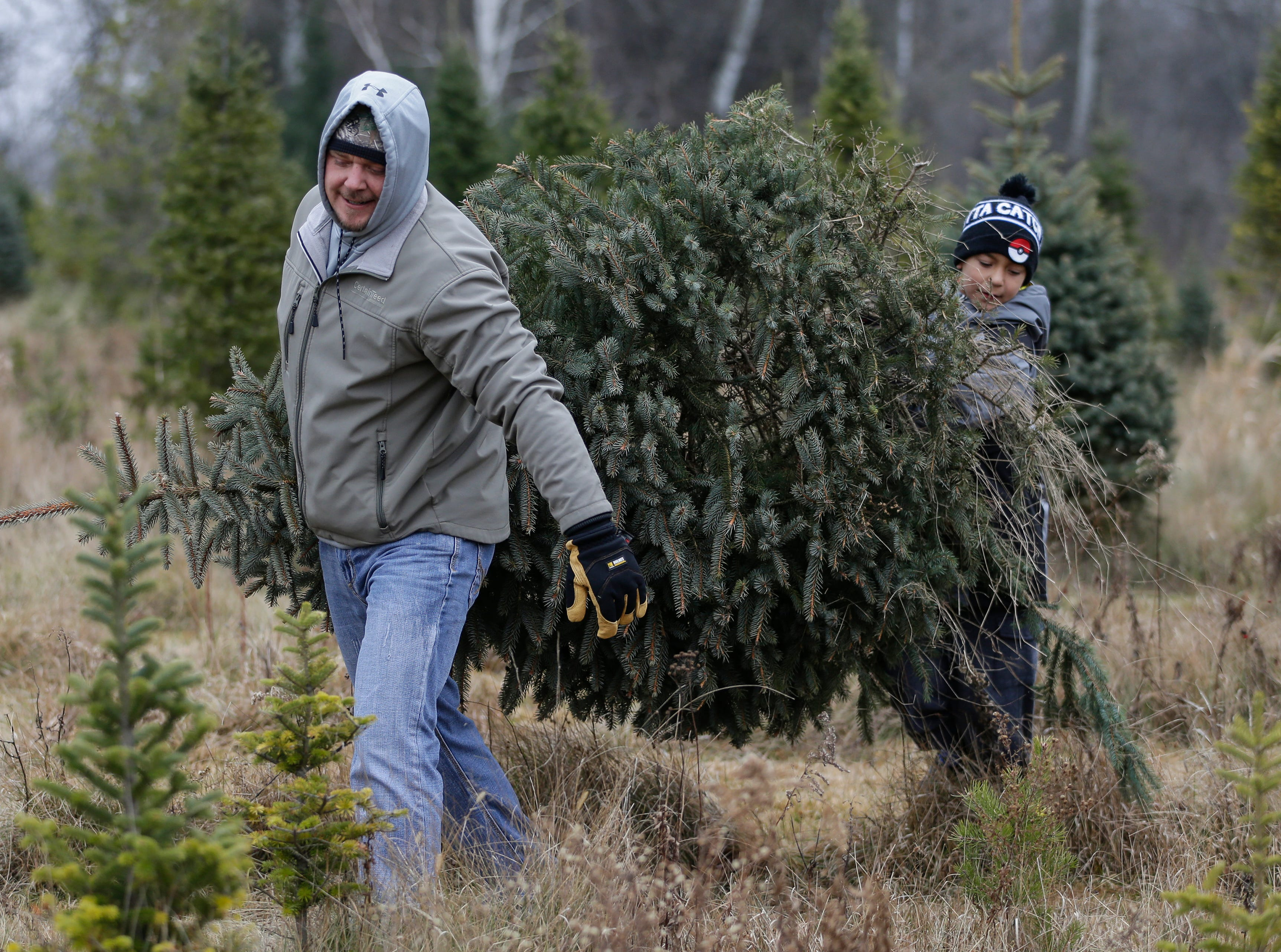 Andy Zigmunt, of Manitowoc, carries a freshly cut Christmas tree with his son Andrew, 11, at Taylor Trees Saturday, December 1, 2018, in Mishicot, Wis. Joshua Clark/USA TODAY NETWORK-Wisconsin