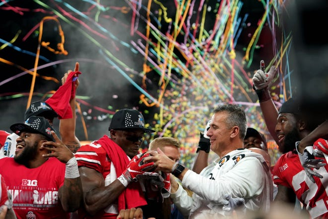 Ohio State coach Urban Meyer hands the Big Ten championship trophy to wide receiver Terry McLaurin, who caught two touchdown passes back in his hometown.