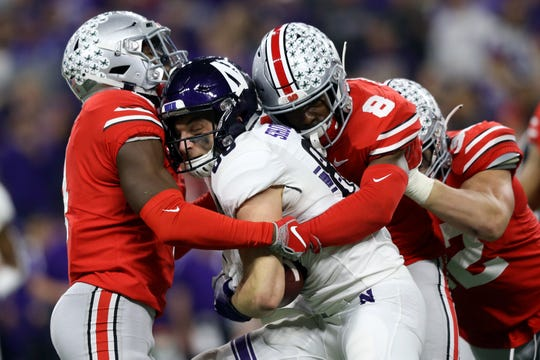 Ohio State safety Jordan Fuller (left) and cornerback Kendall Sheffield sandwich Northwestern receiver Bennett Skowronek in the first half of the Buckeyes' 45-24 victory.