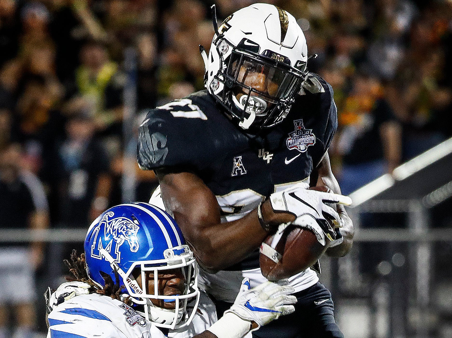 Memphis running back Darrell Henderson (left) can not stop UCF defender Richie Grant (right) from snagging an interception in the end zone to give the Knights a 56-41 viceroy in the AAC Championship Football game Saturday, December 1, 2018 in Orlando.