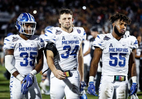 Dejected Memphis teammates (left to right) Tim Hart, Jackson Dillon and Bryce Huff walk off the field after falling to UCF 56-41 in the AAC Championship Football game Saturday, December 1, 2018 in Orlando.
