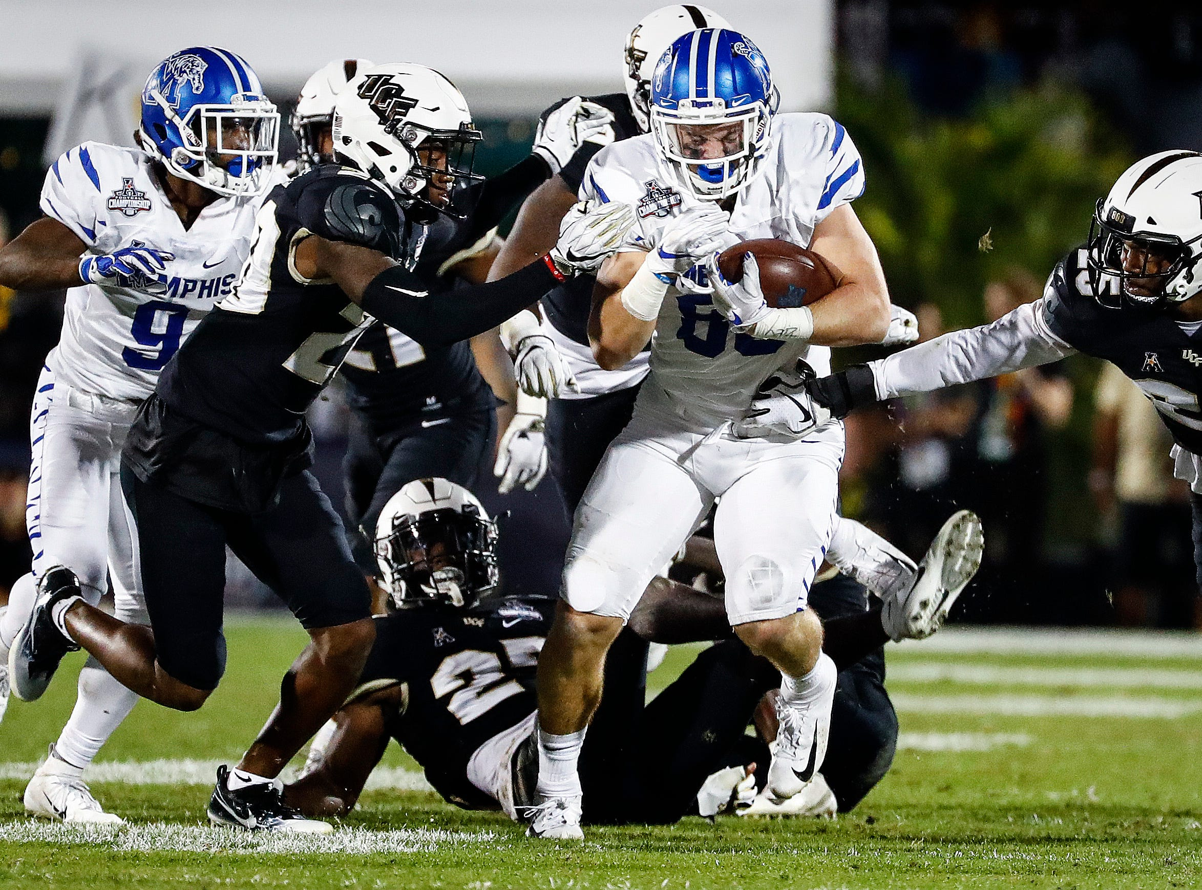 Memphis tight end Joey Magnifico (middle) fights for a first down against the UCF defense during action at the AAC Championship Football game Saturday, December 1, 2018 in Orlando.