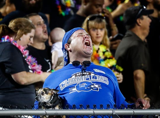 A dejected Memphis fans holding his dog, reacts during the final minutes of a 56-41 loss to UCF in the AAC Championship Football game Saturday, December 1, 2018 in Orlando.