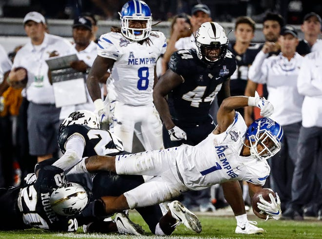 Memphis running back Tony Pollard (right) fights for yards against Central Florida on Saturday in the AAC Championship game.