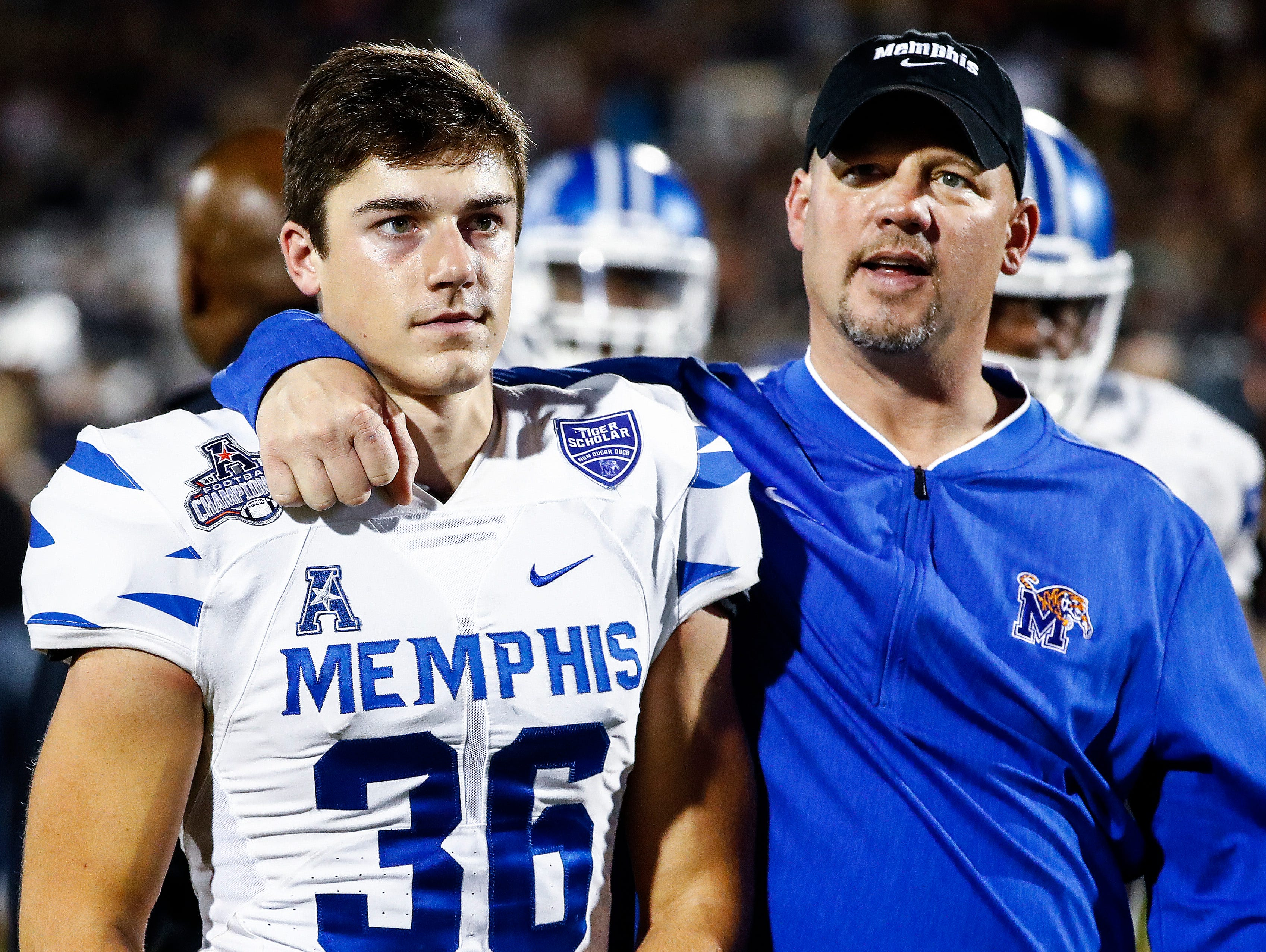 Memphis kicker Riley Patterson (left) and special teams coach Joe Lorig (right) walk off the field after falling to UCF 56-41 in the AAC Championship Football game Saturday, December 1, 2018 in Orlando.