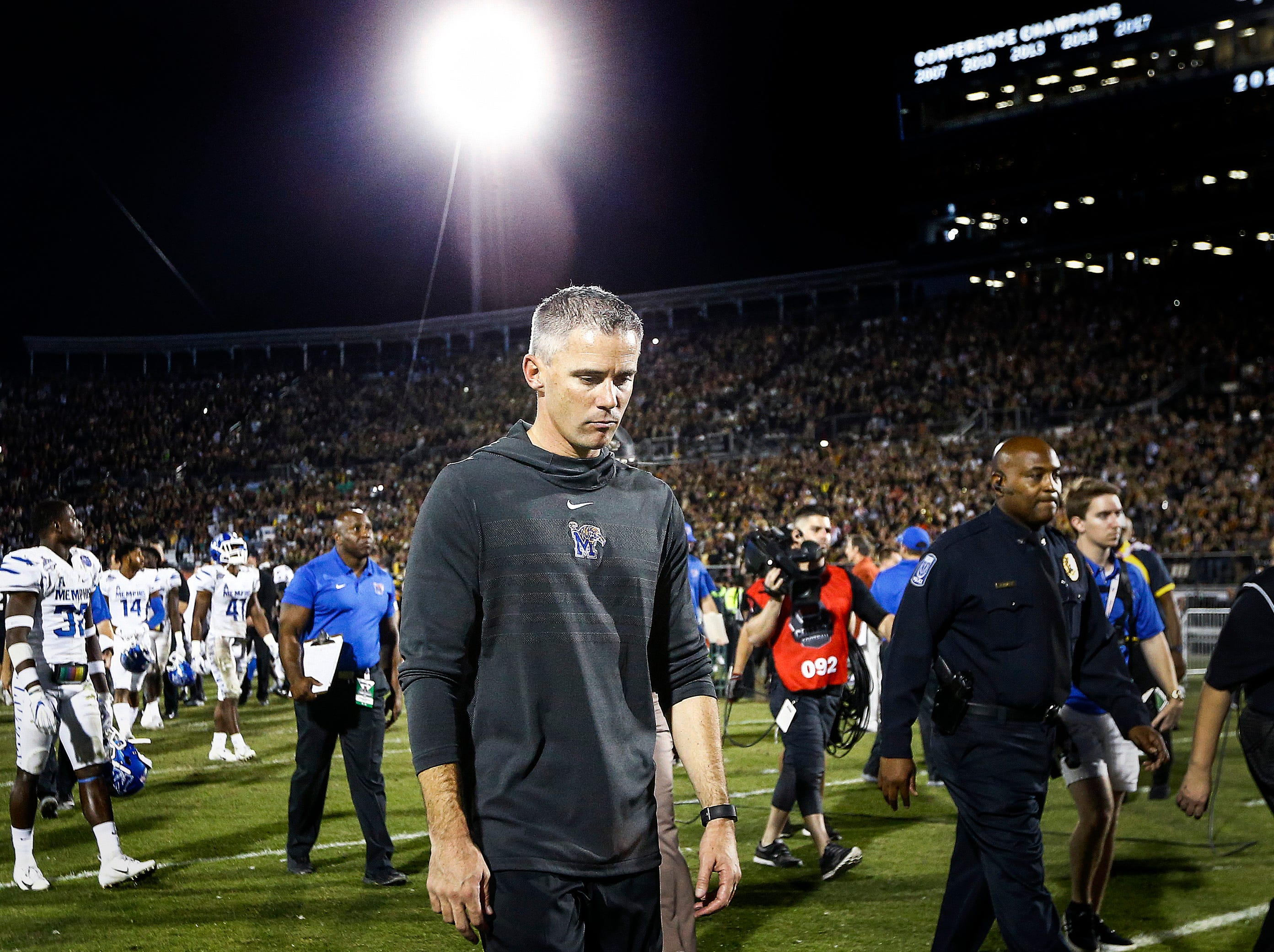 Dejected Memphis head coach Mike Norvell walks off the field after falling to UCF 56-41 in the AAC Championship Football game Saturday, December 1, 2018 in Orlando.