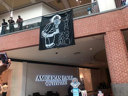 A group hung banners in Wolfchase Galleria on Saturday, Dec. 2, 2018, to protest mall policies after the arrest last month of two black males there.