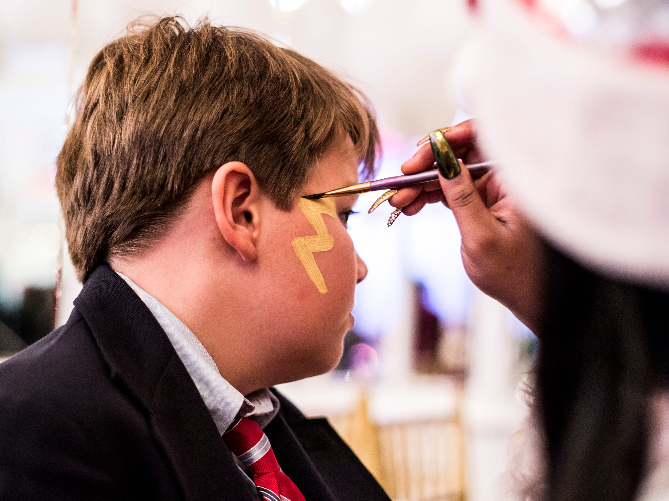 December 02 2018 - Garrett Johnson, 10, gets a lightning bolt painted on his face during the Memphis Jingle Bell Ball Holiday Cookie Party inside of the Continental Ballroom at the Peabody Hotel on Sunday. This was the 30th anniversary of the Jingle Bell Ball.