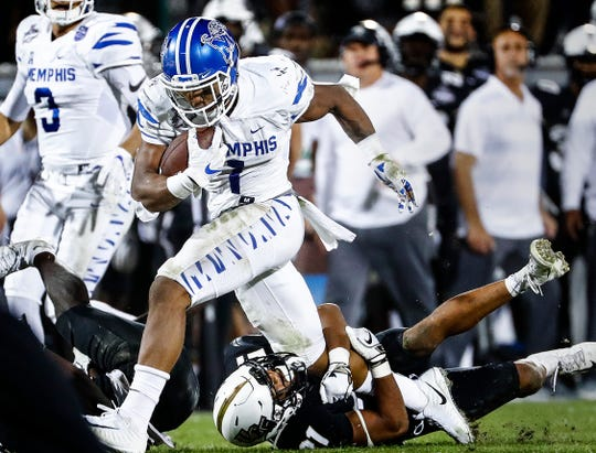 Memphis running back Tony Pollard runs over UCF defender Rashard Causey (bottom) during action at the AAC Championship Football game Saturday, December 1, 2018 in Orlando.