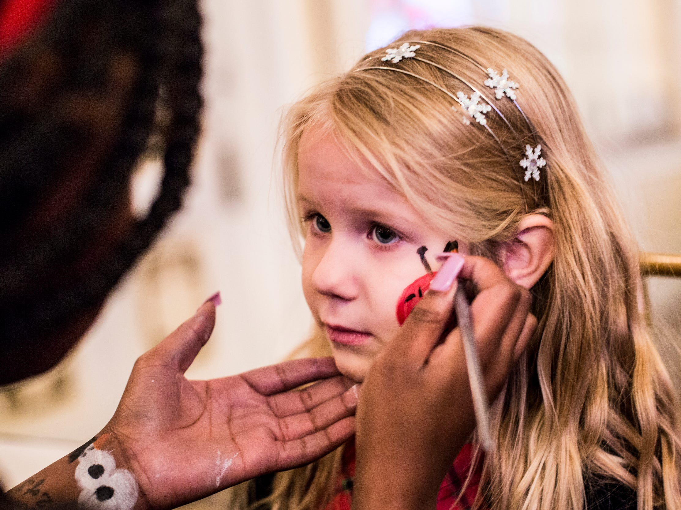 December 02 2018 - Jonna Bryant, left, paints a ladybug onto Shelby Ray, 4, during the Memphis Jingle Bell Ball Holiday Cookie Party inside of the Continental Ballroom at the Peabody Hotel on Sunday. This was the 30th anniversary of the Jingle Bell Ball.