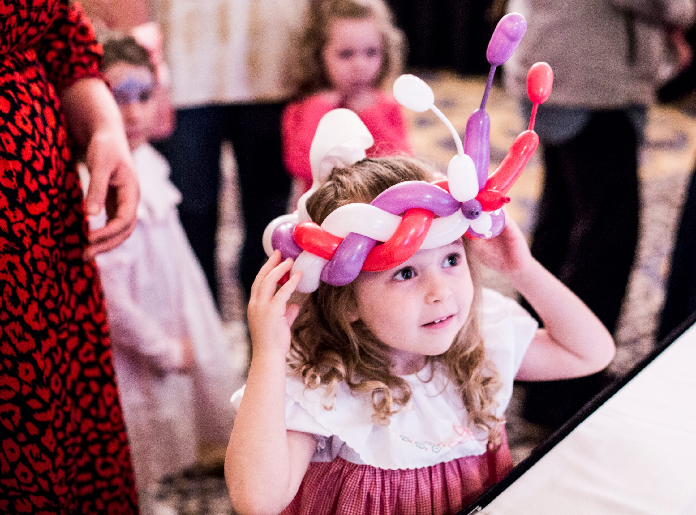 December 02 2018 - Rose Walker, 4, tries on her balloon crown during the Memphis Jingle Bell Ball Holiday Cookie Party inside of the Continental Ballroom at the Peabody Hotel on Sunday. This was the 30th anniversary of the Jingle Bell Ball.