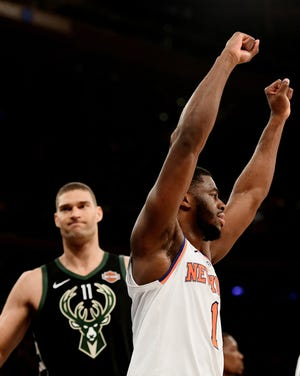 Emmanuel Mudiay celebrates as Brook Lopez grimaces after the Knicks rallied to beat the Bucks in overtime on Saturday at Madison Square Garden. Mudiay led New York with 28 points and played a big role in the Knicks' 20-of-34 performance from three-point territory.