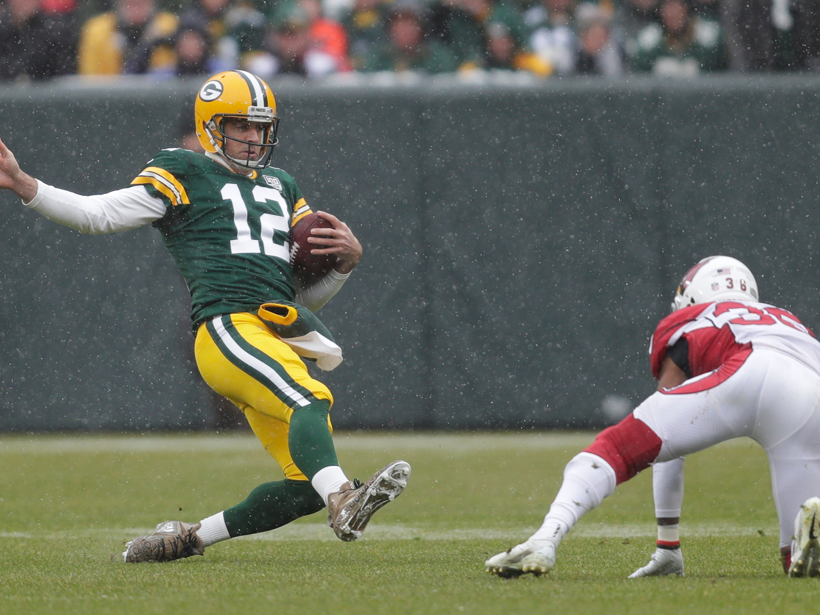 Green Bay Packers quarterback Aaron Rodgers (12) slides for yardage against Arizona Cardinals strong safety Budda Baker (36) in the first quarter Sunday, December 2, 2018, at Lambeau Field in Green Bay, Wis.