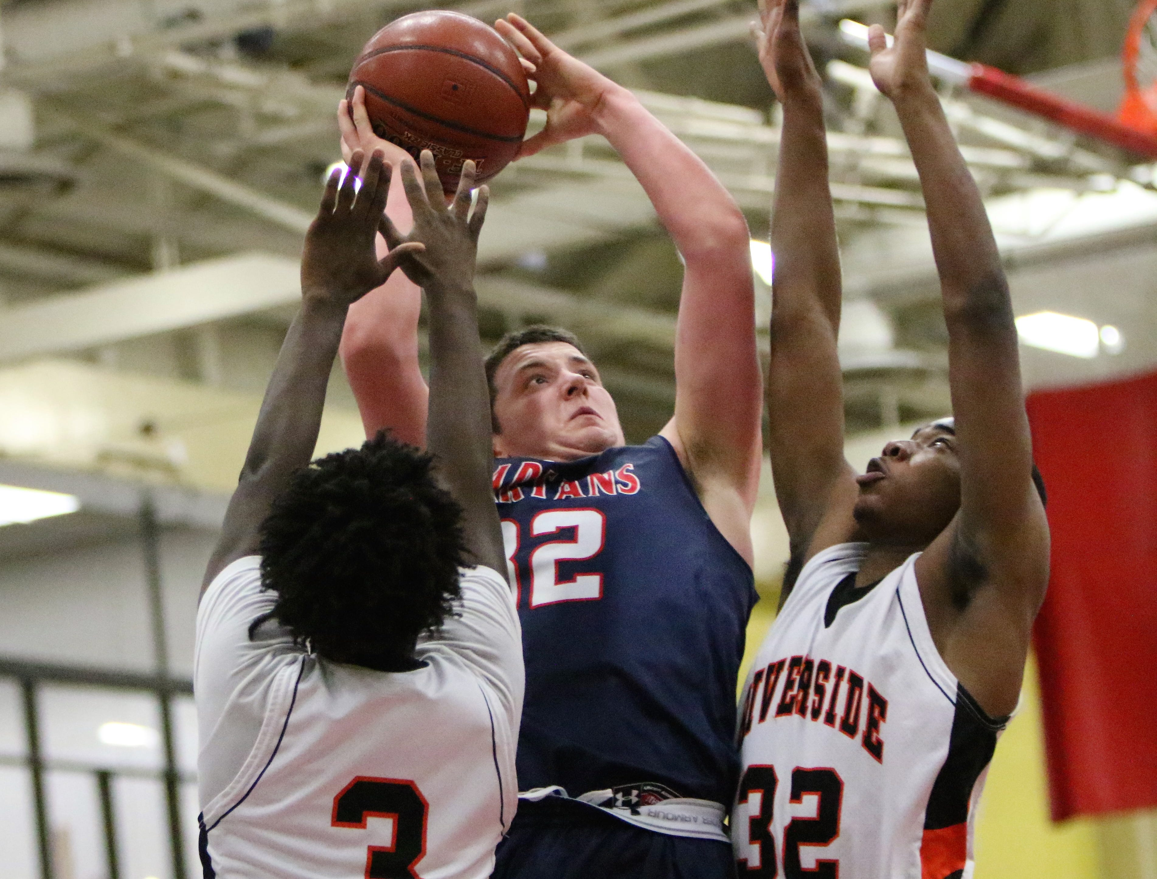 Brookfield East forward Riley LeTourneau goes up for a shot near the rim over Milwaukee Riverside defenders Leo Davis (3) and Brandon Dodds (32).