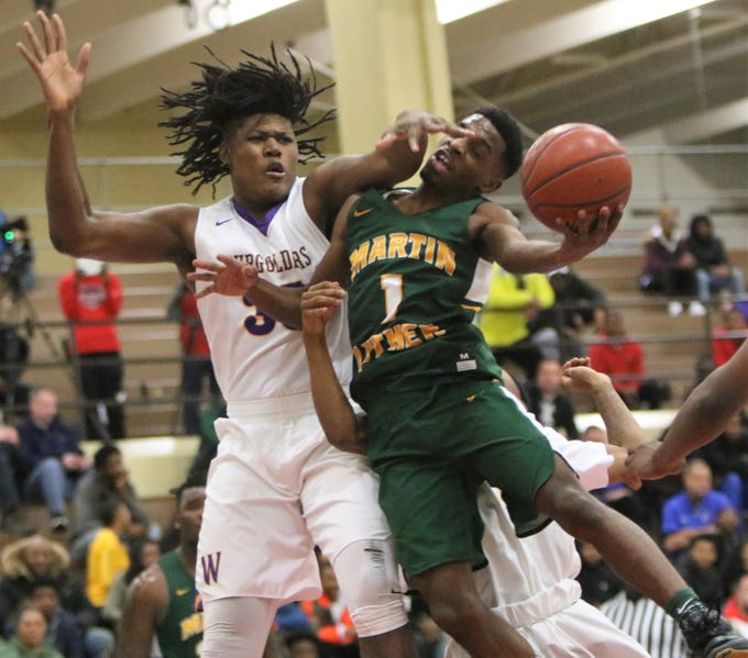 Martin Luther guard Trequan Carrington  tries to avoid the reach of Milwaukee Washington's Jimmy Brown Jr. during the Terry Porter Classic on Saturday, Dec. 1.