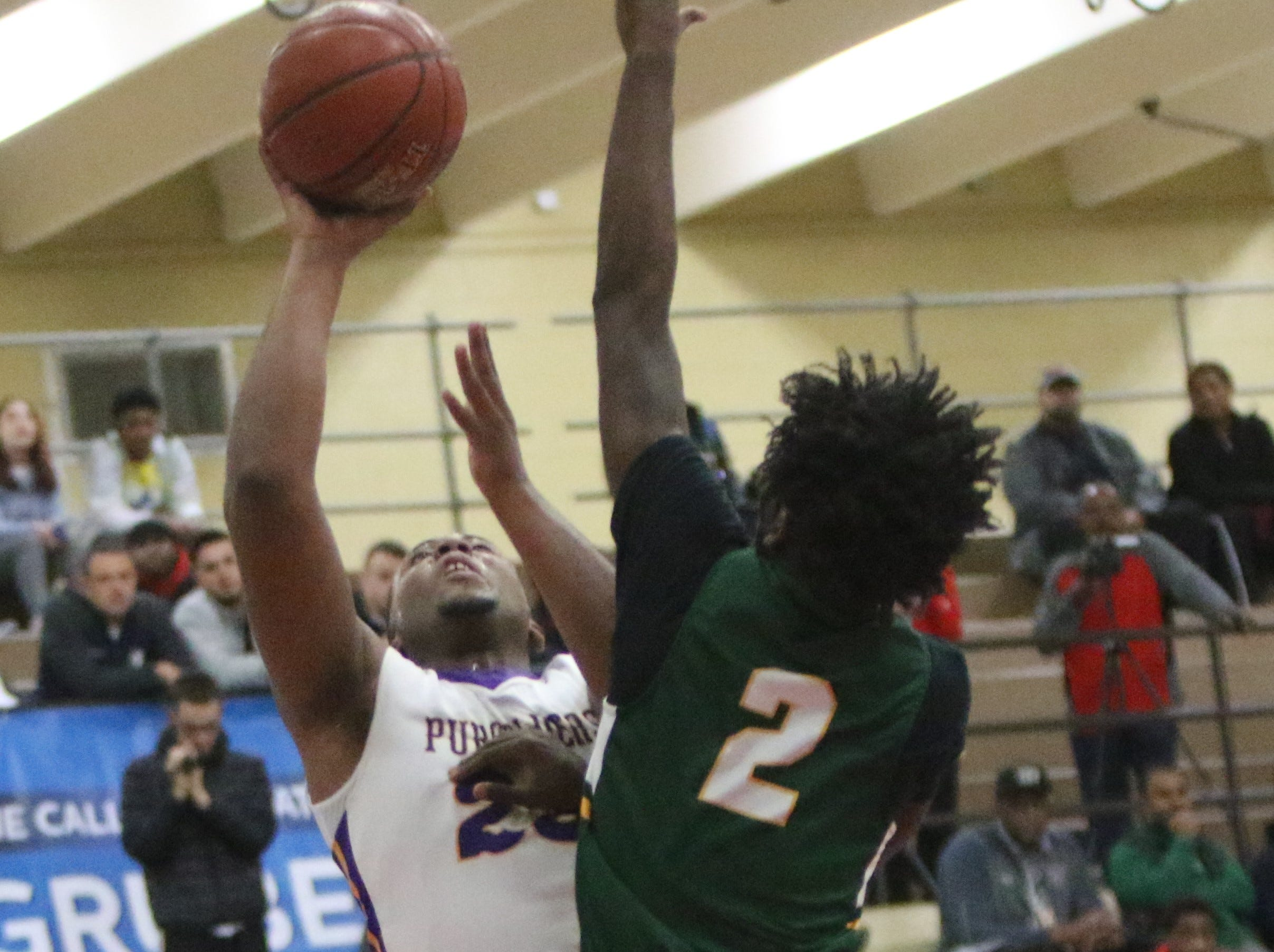 Martin Luther guard Ace Evans blocks the shot of Milwaukee Washington's Johntae Martin during the Terry Porter Classic on Saturday.