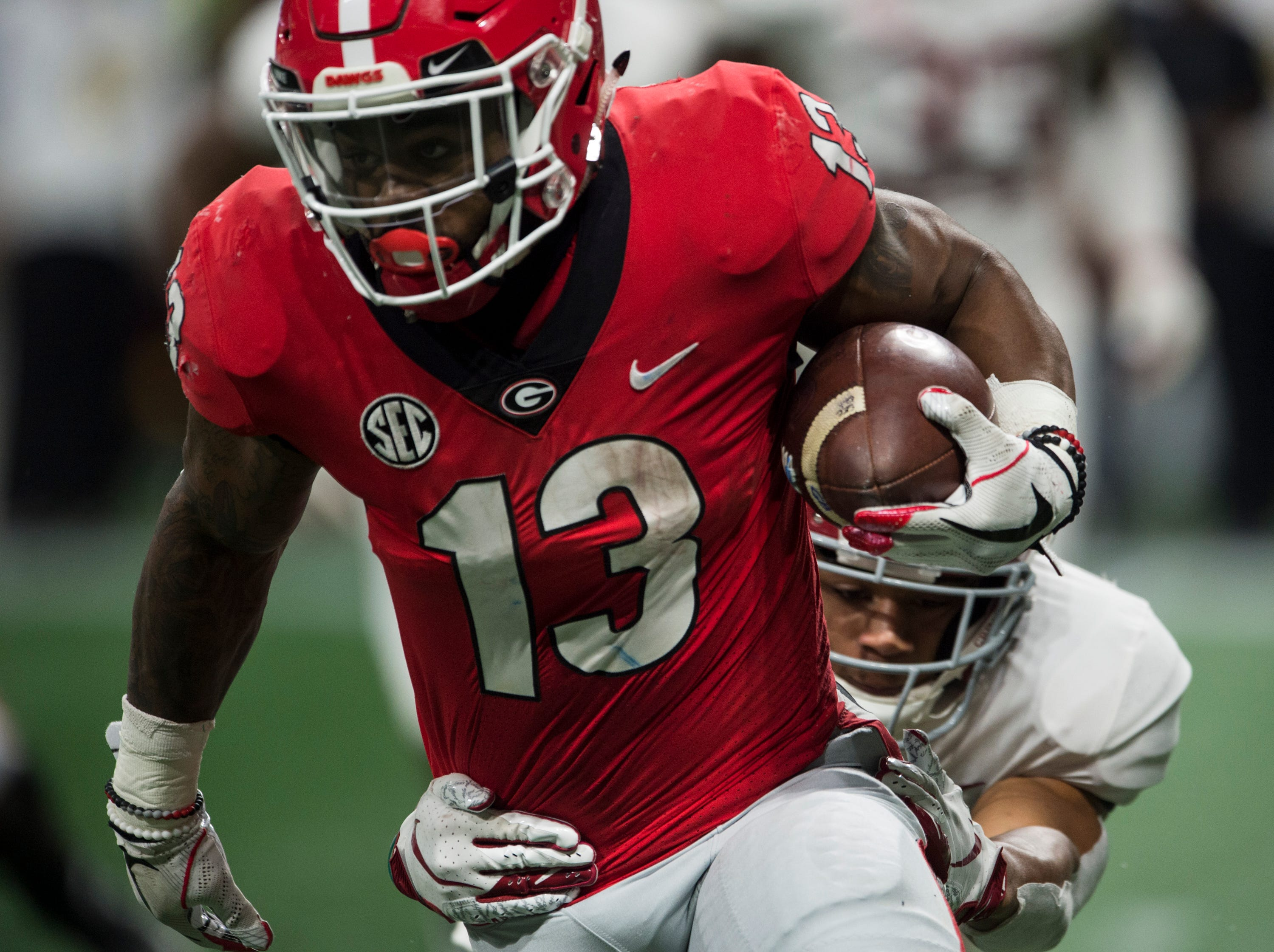 Georgia running back Elijah Holyfield (13) runs the ball against Alabama during the SEC Championship game at Mercedes-Benz Stadium in Atlanta, Ga., on Saturday Dec. 1, 2018. Alabama defeated Georgia 35-28.