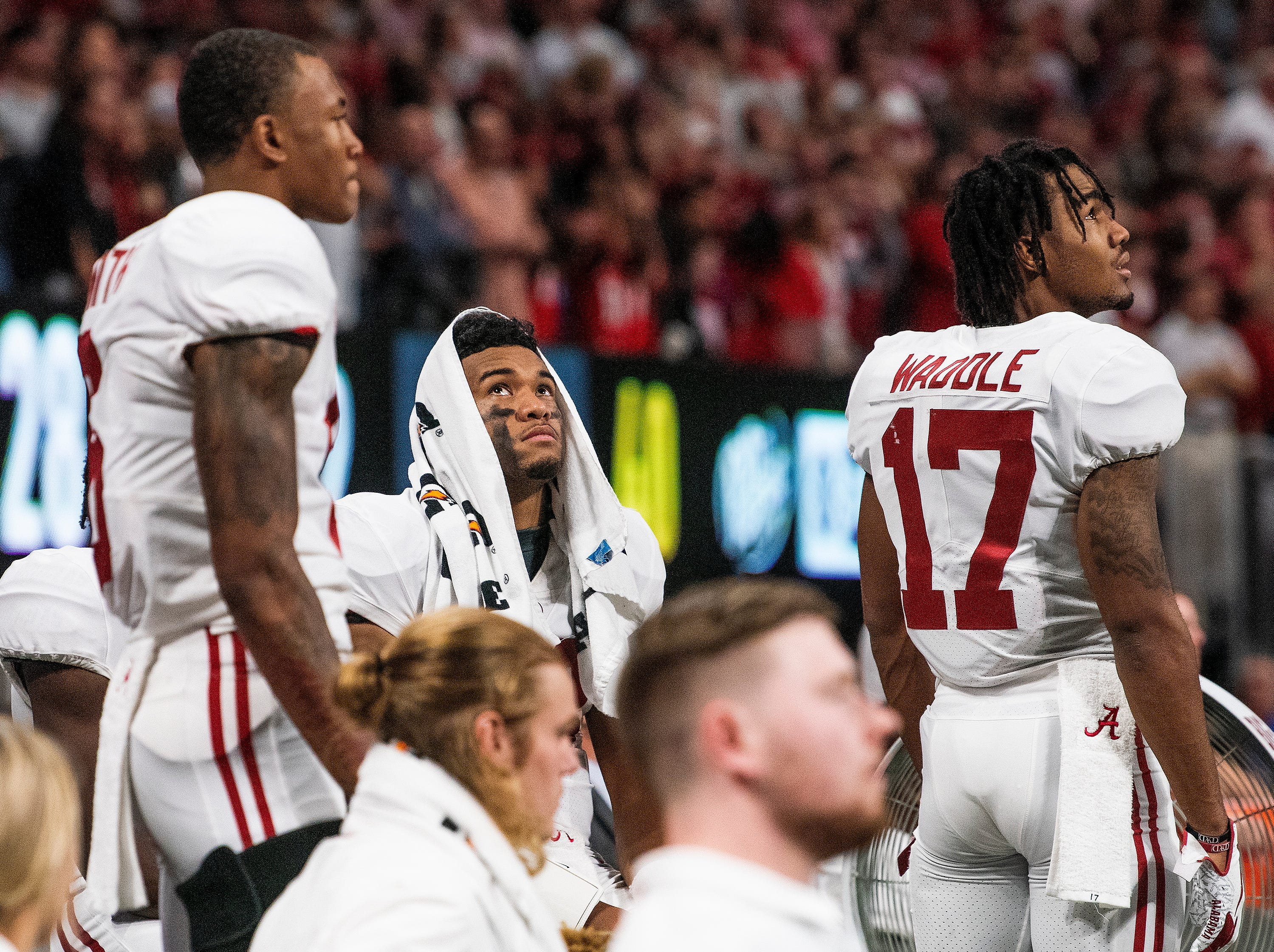 Alabama quarterback Tua Tagovailoa (13), center, watches the final minute of the SEC Championship Game from the bench after being injured at Mercedes Benz Stadium in Atlanta, Ga., on Saturday December 1, 2018.