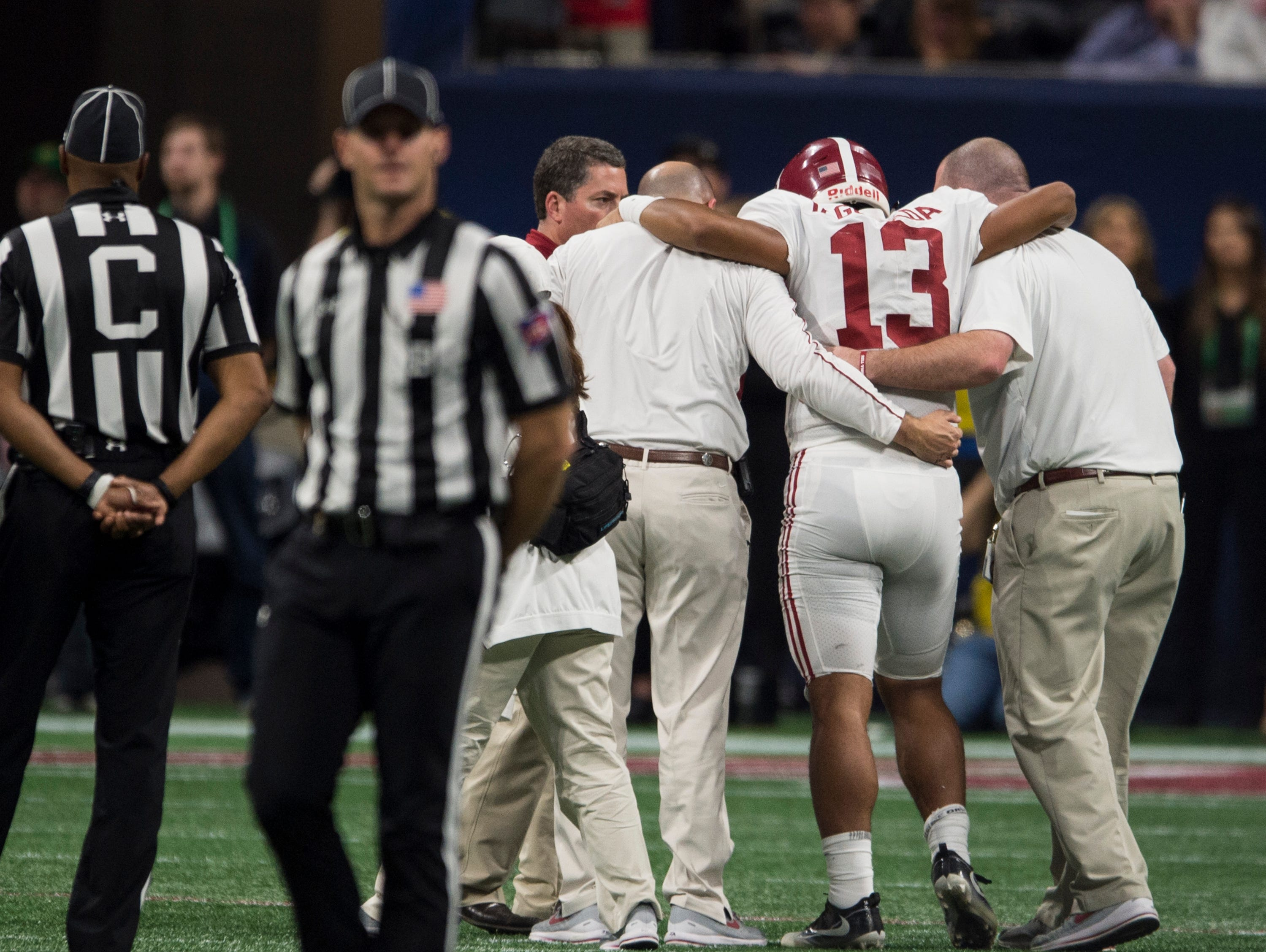 Alabama quarterback Tua Tagovailoa (13) is help off the field after suffering an injury during the SEC Championship game at Mercedes-Benz Stadium in Atlanta, Ga., on Saturday Dec. 1, 2018. Alabama defeated Georgia 35-28.