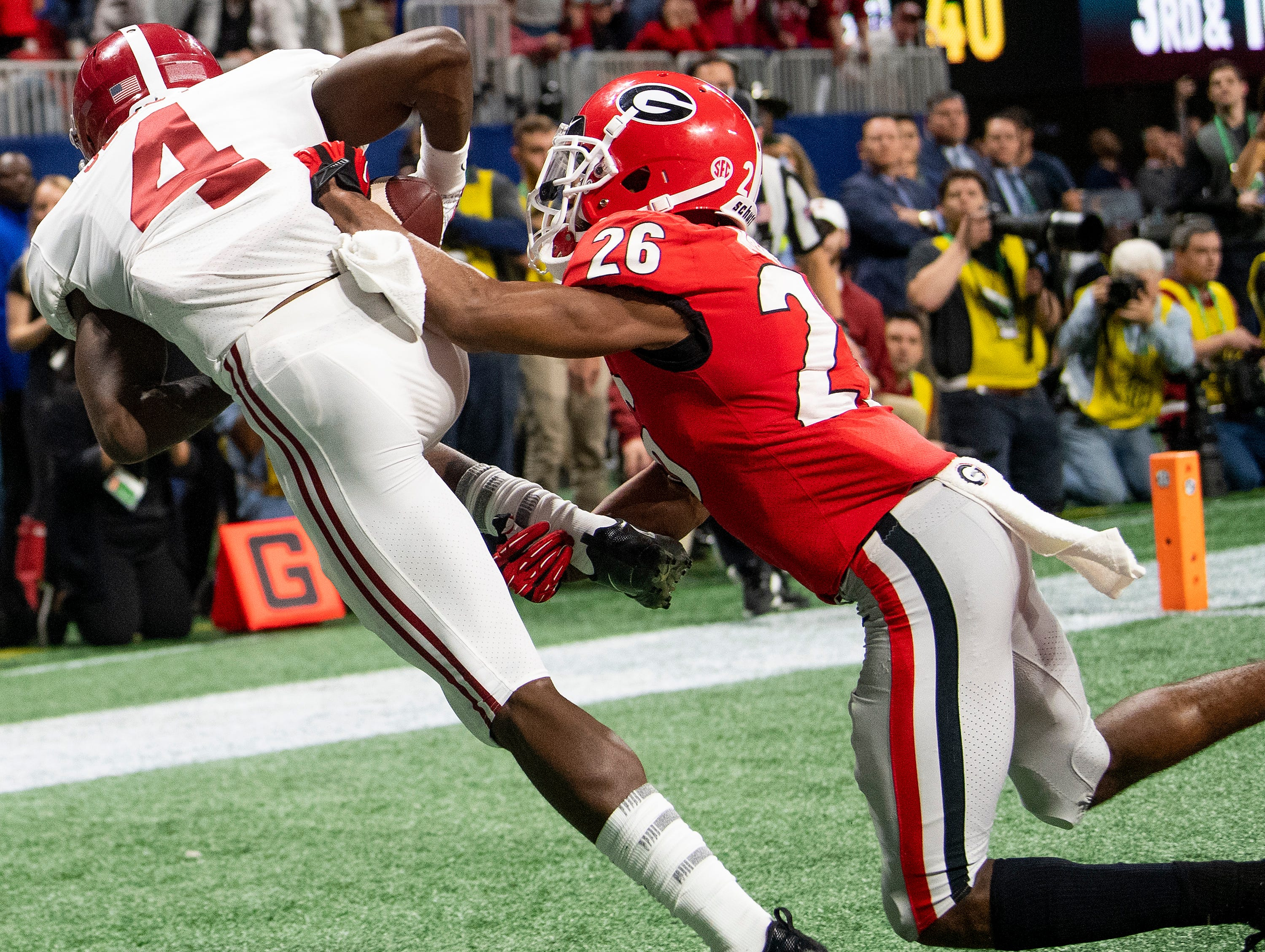 Alabama wide receiver Jerry Jeudy (4) catches a touchdown pass against Georgia defensive back Tyrique McGhee (26) late in the SEC Championship Game at Mercedes Benz Stadium in Atlanta, Ga., on Saturday December 1, 2018.