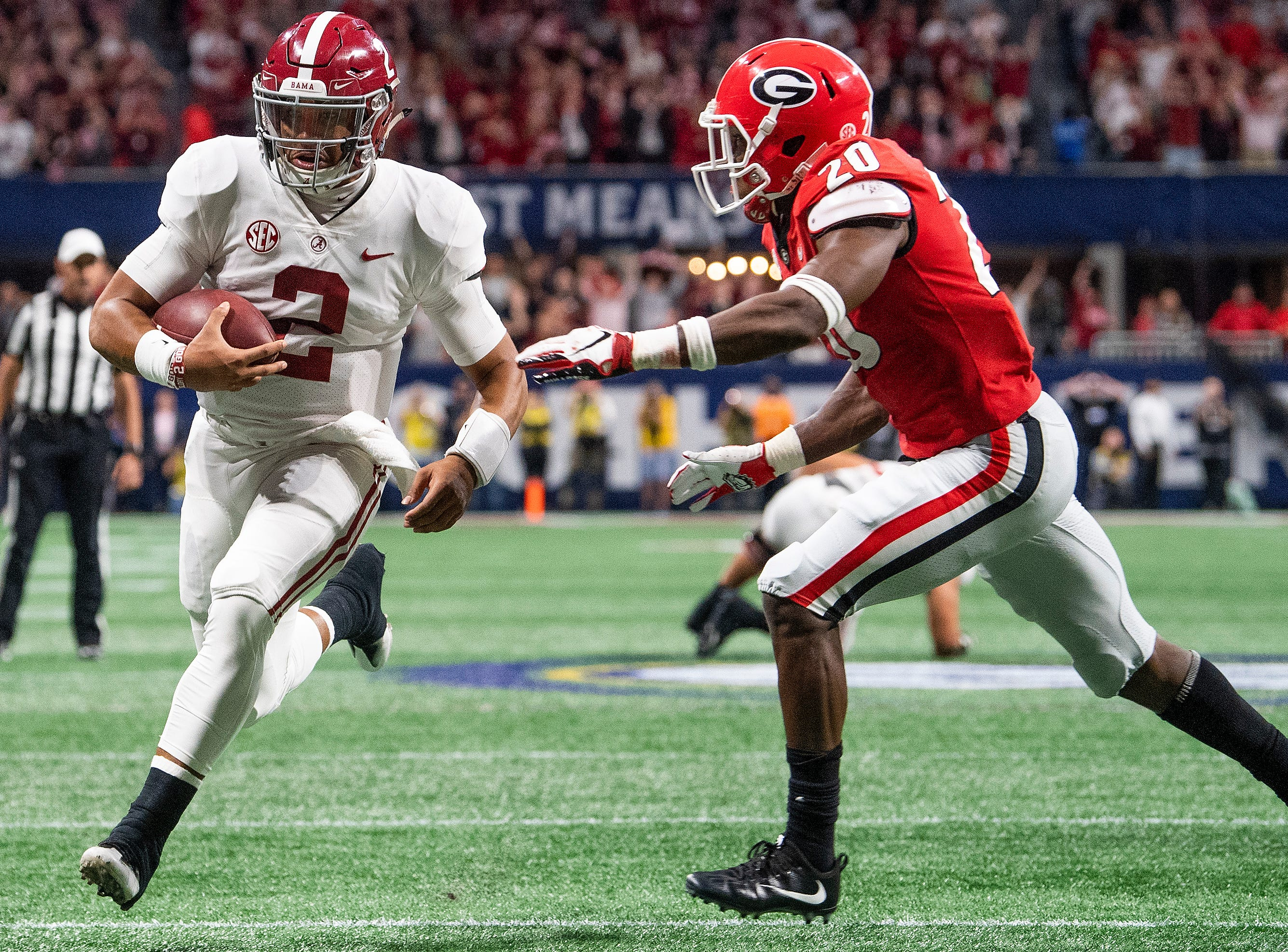 Alabama quarterback Jalen Hurts (2) scores the go ahead touchdown against Georgia defensive back J.R. Reed (20) in the SEC Championship Game at Mercedes Benz Stadium in Atlanta, Ga., on Saturday December 1, 2018.