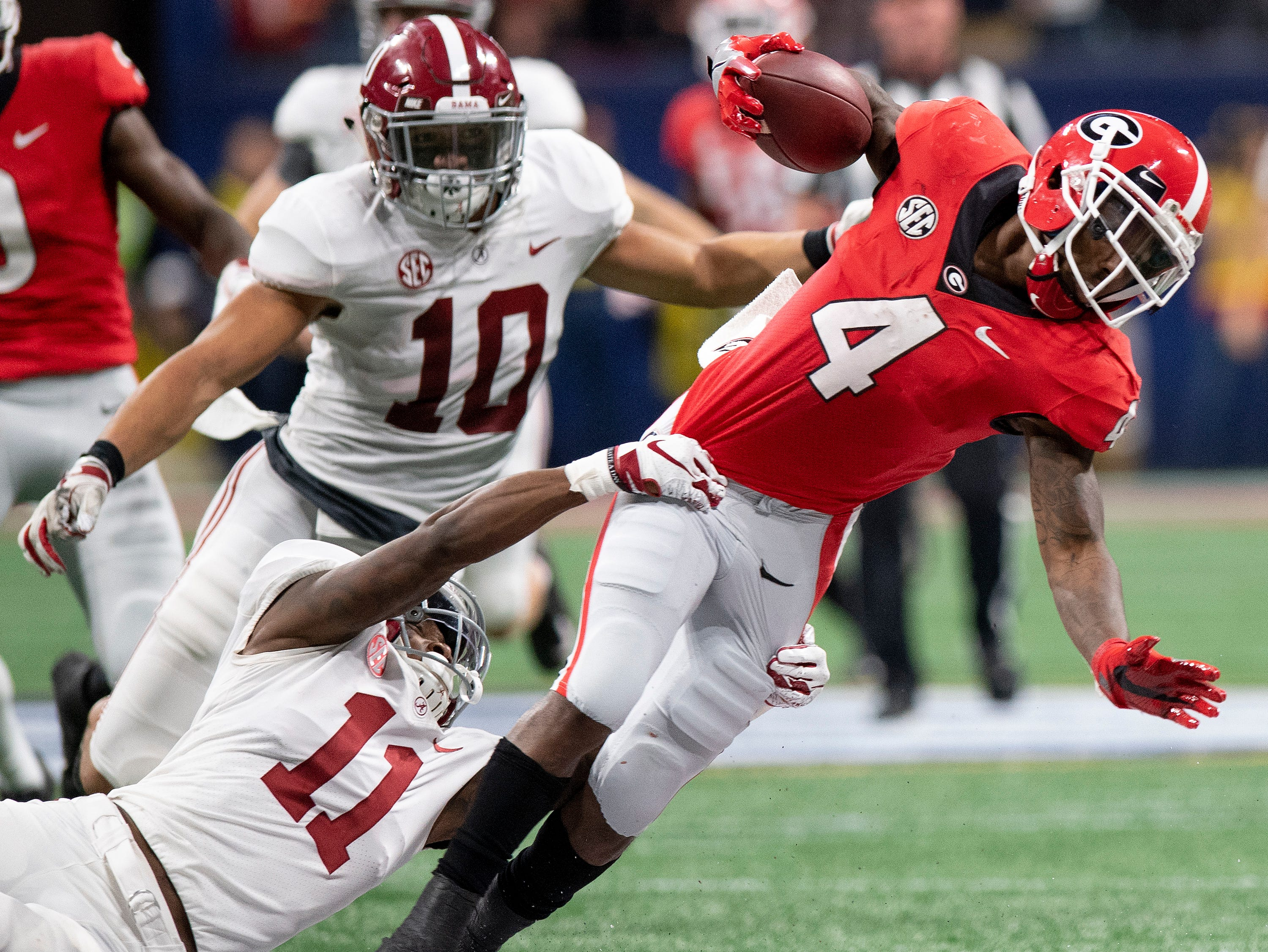 Alabama wide receiver Henry Ruggs, III, (11) stops Georgia wide receiver Mecole Hardman (4) on a kick return in the SEC Championship Game at Mercedes Benz Stadium in Atlanta, Ga., on Saturday December 1, 2018.