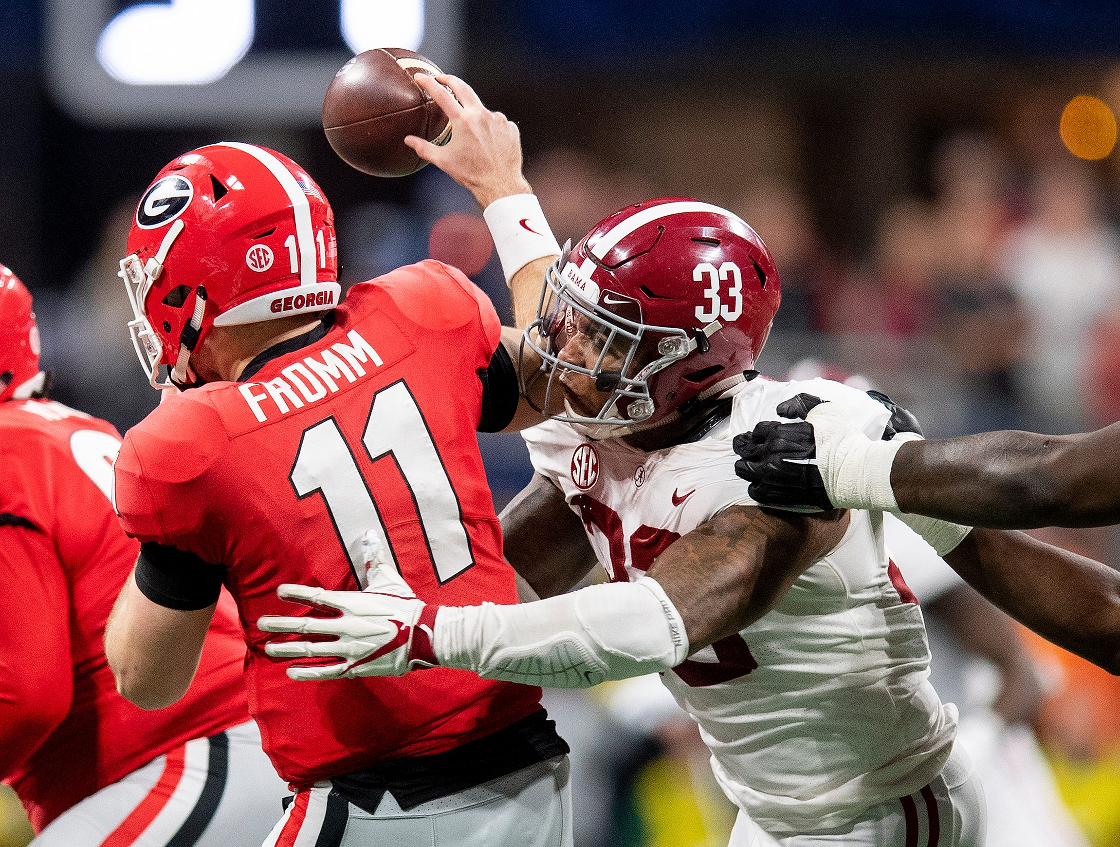 Alabama linebacker Anfernee Jennings (33) hits Georgia quarterback Jake Fromm (11) causing the pass to fall incomplete late in the SEC Championship Game at Mercedes Benz Stadium in Atlanta, Ga., on Saturday December 1, 2018.