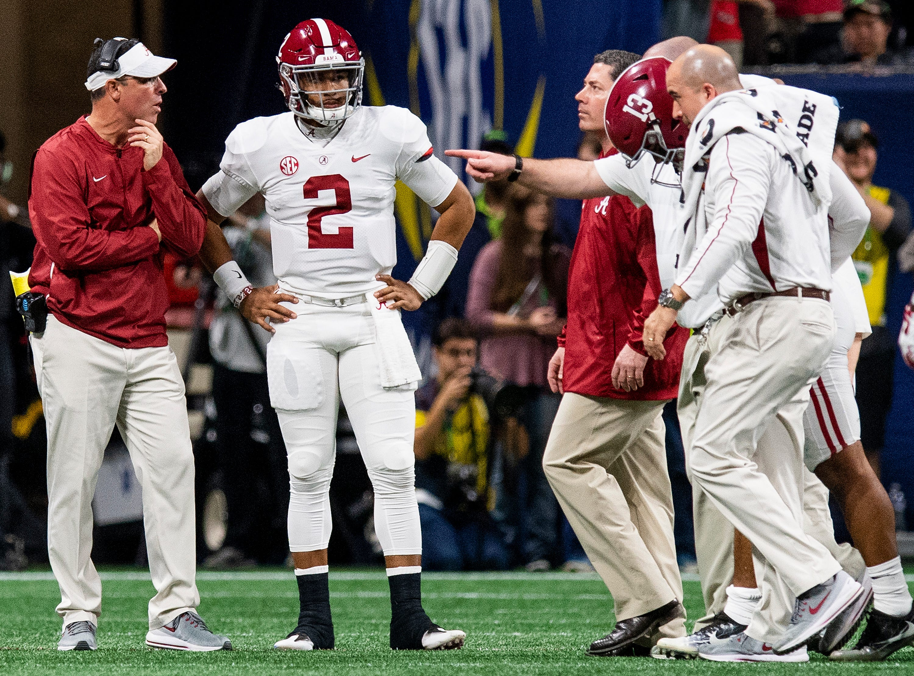 Injured Alabama quarterback Tua Tagovailoa (13) is helped off the field as quarterback Jalen Hurts (2) talks with quarterbacks coach Dan Enos in the SEC Championship Game at Mercedes Benz Stadium in Atlanta, Ga., on Saturday December 1, 2018.