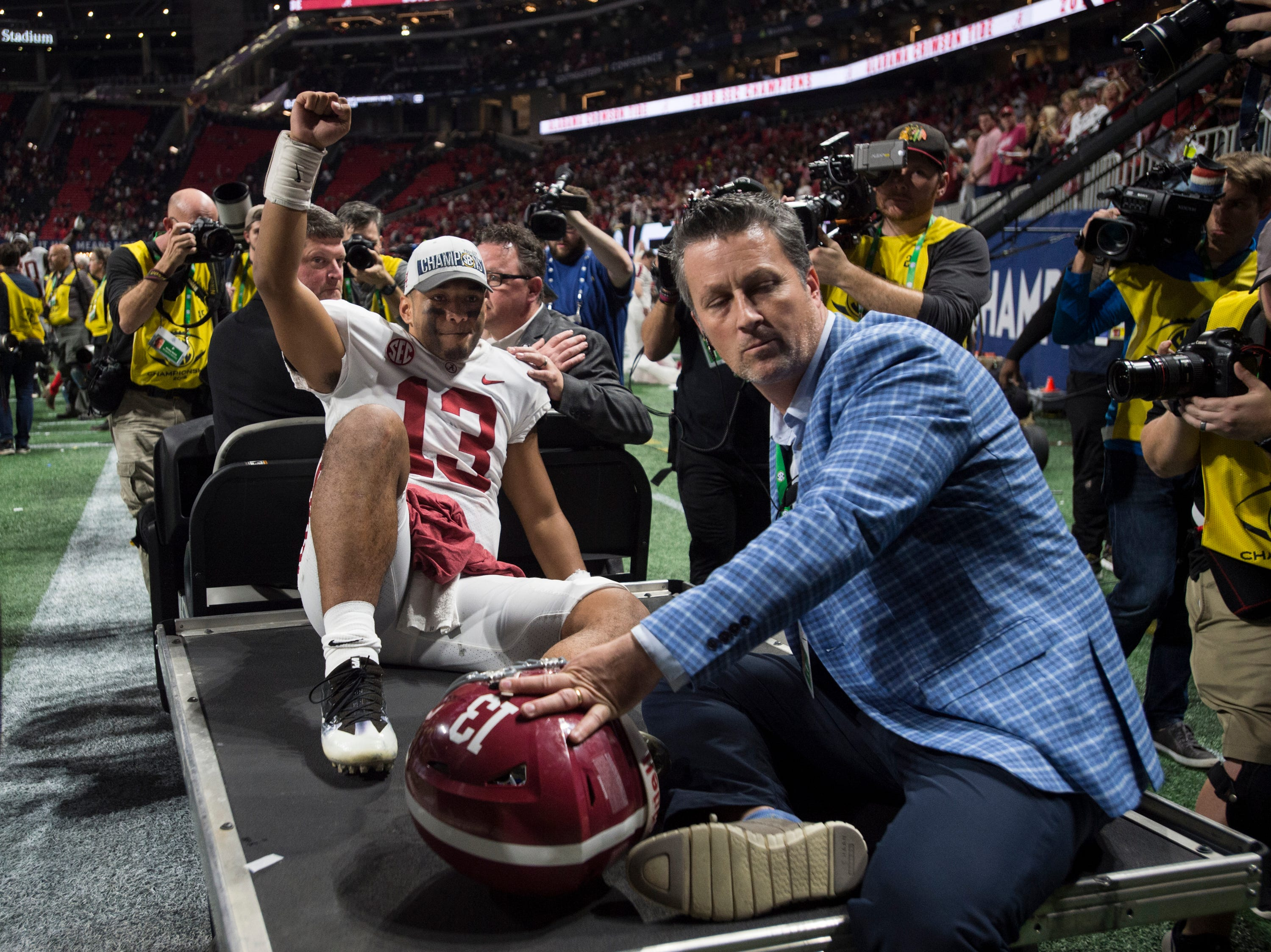 Alabama quarterback Tua Tagovailoa (13) acknowledges the fans as he is carted off the field during the SEC Championship game at Mercedes-Benz Stadium in Atlanta, Ga., on Saturday Dec. 1, 2018. Alabama defeated Georgia 35-28.