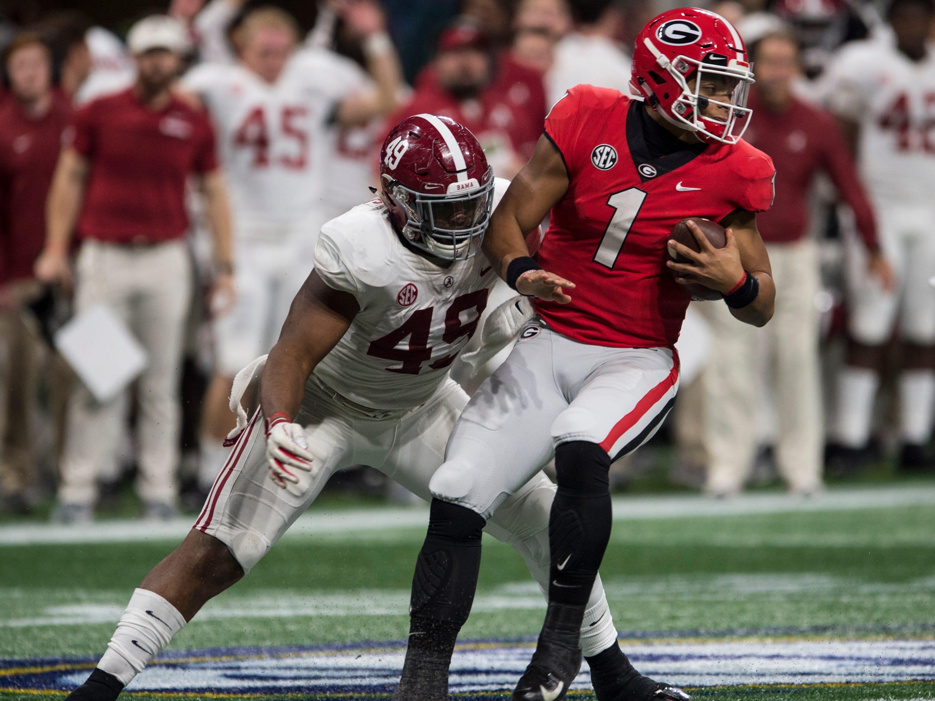 Georgia quarterback Justin Fields (1) is taken down by Alabama defensive lineman Isaiah Buggs (49) during the SEC Championship game at Mercedes-Benz Stadium in Atlanta, Ga., on Saturday Dec. 1, 2018. Alabama defeated Georgia 35-28.