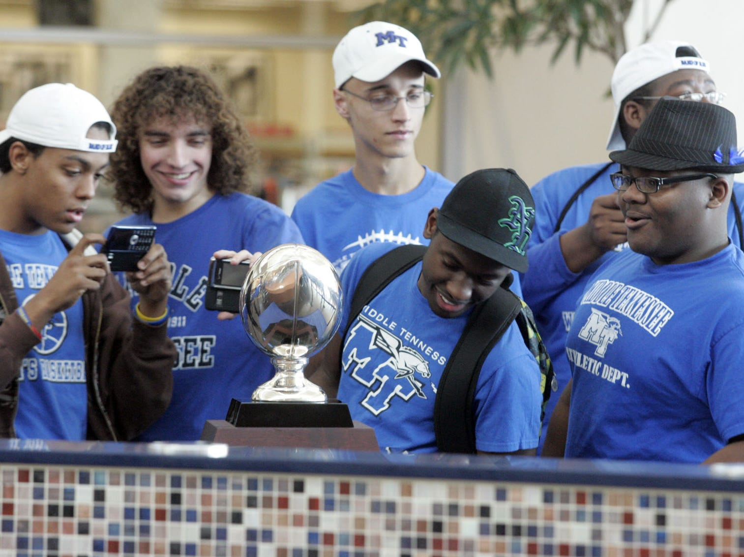 Members of the Band of Blue check out the New Orleans Bowl trophy during the championship celebration at Stones River Mall.