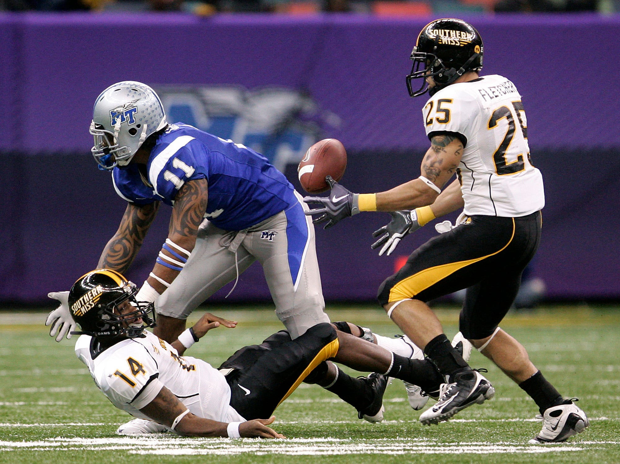 Southern Mississippi's Damion Fletcher (25) retrieves the ball after quarterback Martevious Young (14) fumbled while being tackled by MTSU's Jamari Lattimore (11) during the first half of the New Orleans Bowl on Dec. 20, 2009.