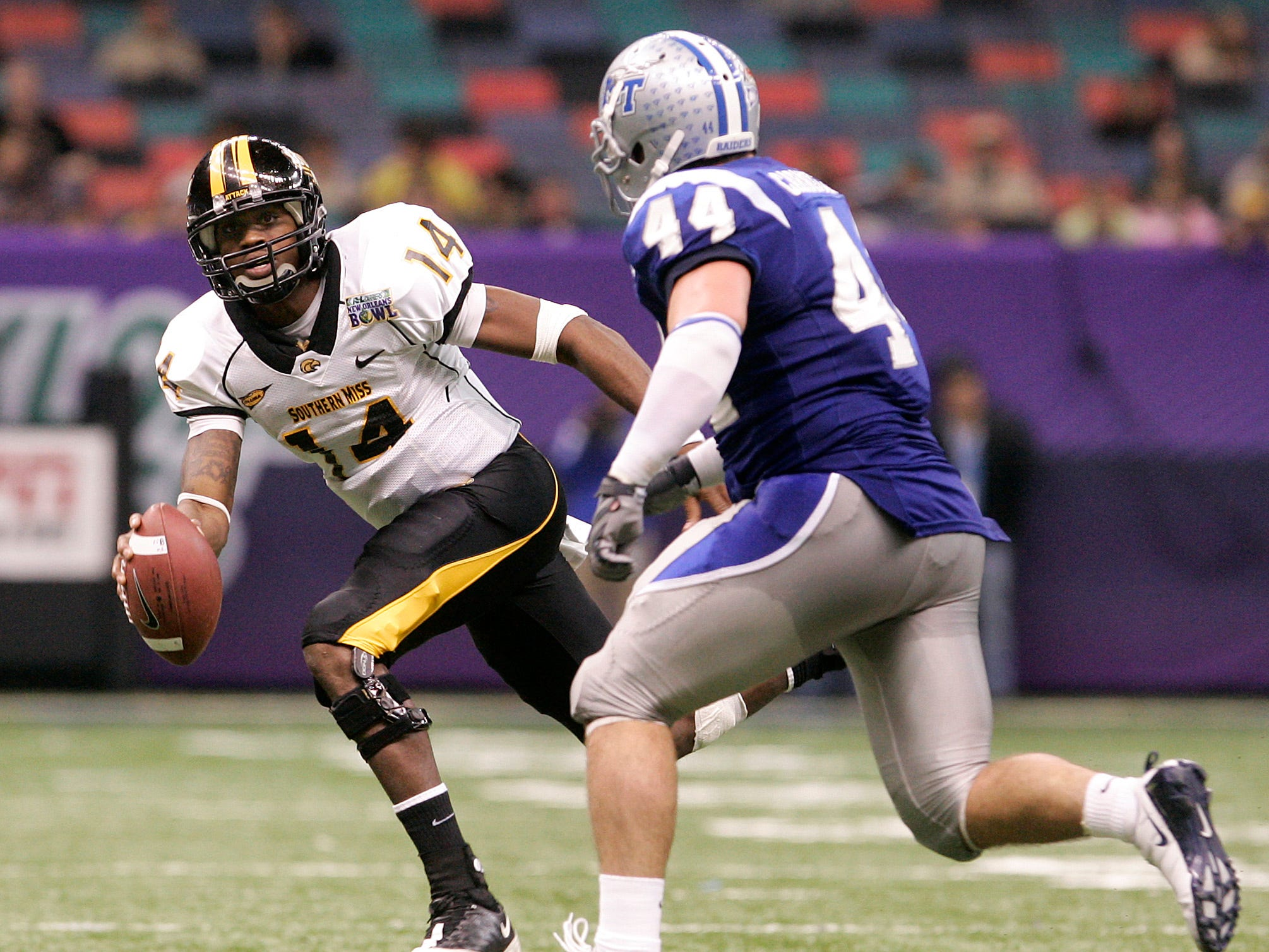 Southern Mississippi quarterback Martevious Young (14) is chased by MTSU linebacker Danny Carmichael (44) during the second half of the New Orleans Bowl on Dec. 20, 2009.